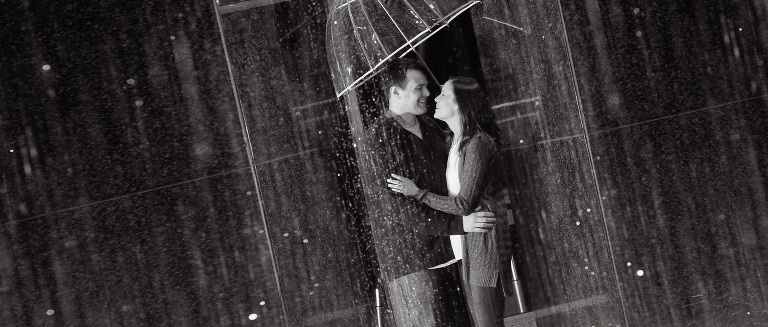 An newly engaged couple stand under a fountain in the rain downtown Detroit.