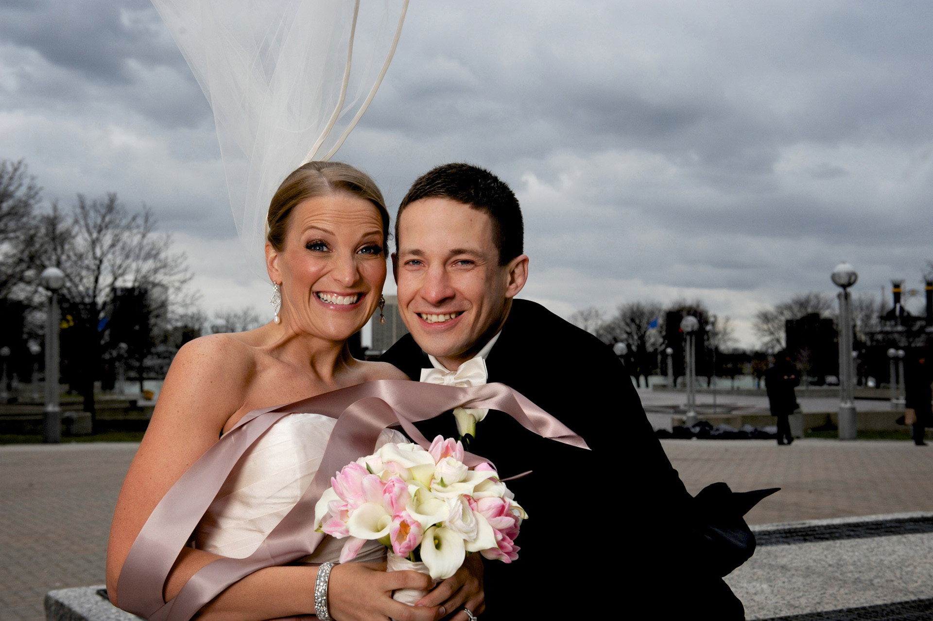 A windy winter wedding in Michigan photographer's photo of bride and groom freezing in the wind after their Michigan wedding in Detroit, Michigan's wedding venue St. Aloysius Detroit, Michigan and the Detroit Athletic Club.