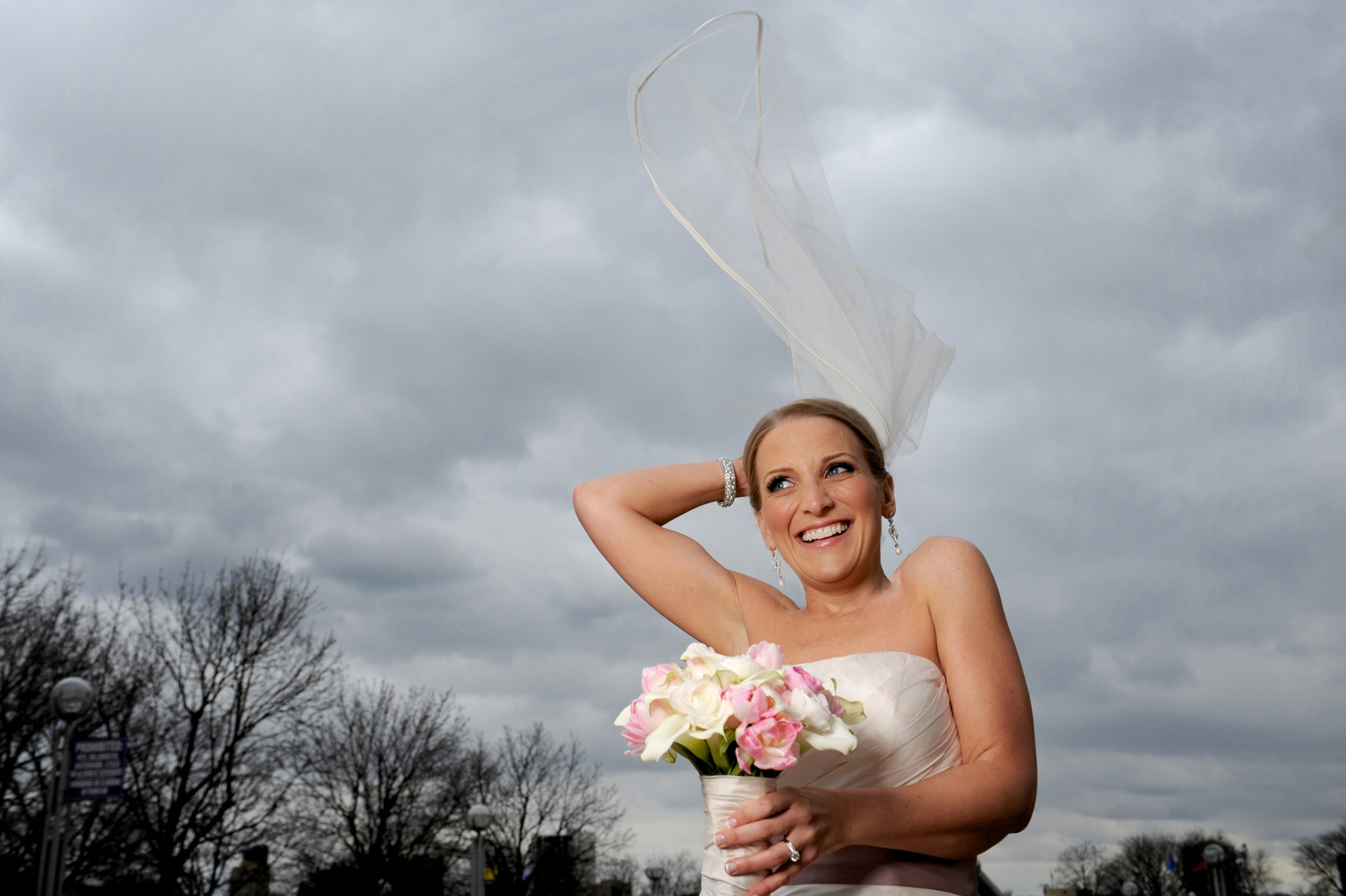 A windy winter wedding in Michigan photographer features the bride reacting as her veil threatens to fly away after her wedding in Detroit, Michigan's wedding venue St. Aloysius Detroit, Michigan and the Detroit Athletic Club.