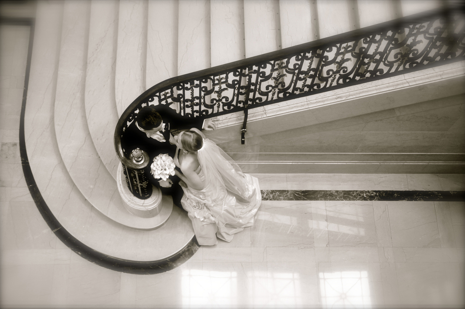 A windy winter wedding in Michigan features a bride and groom having a quiet moment in the stairwell of the Detroit Athletic Club.