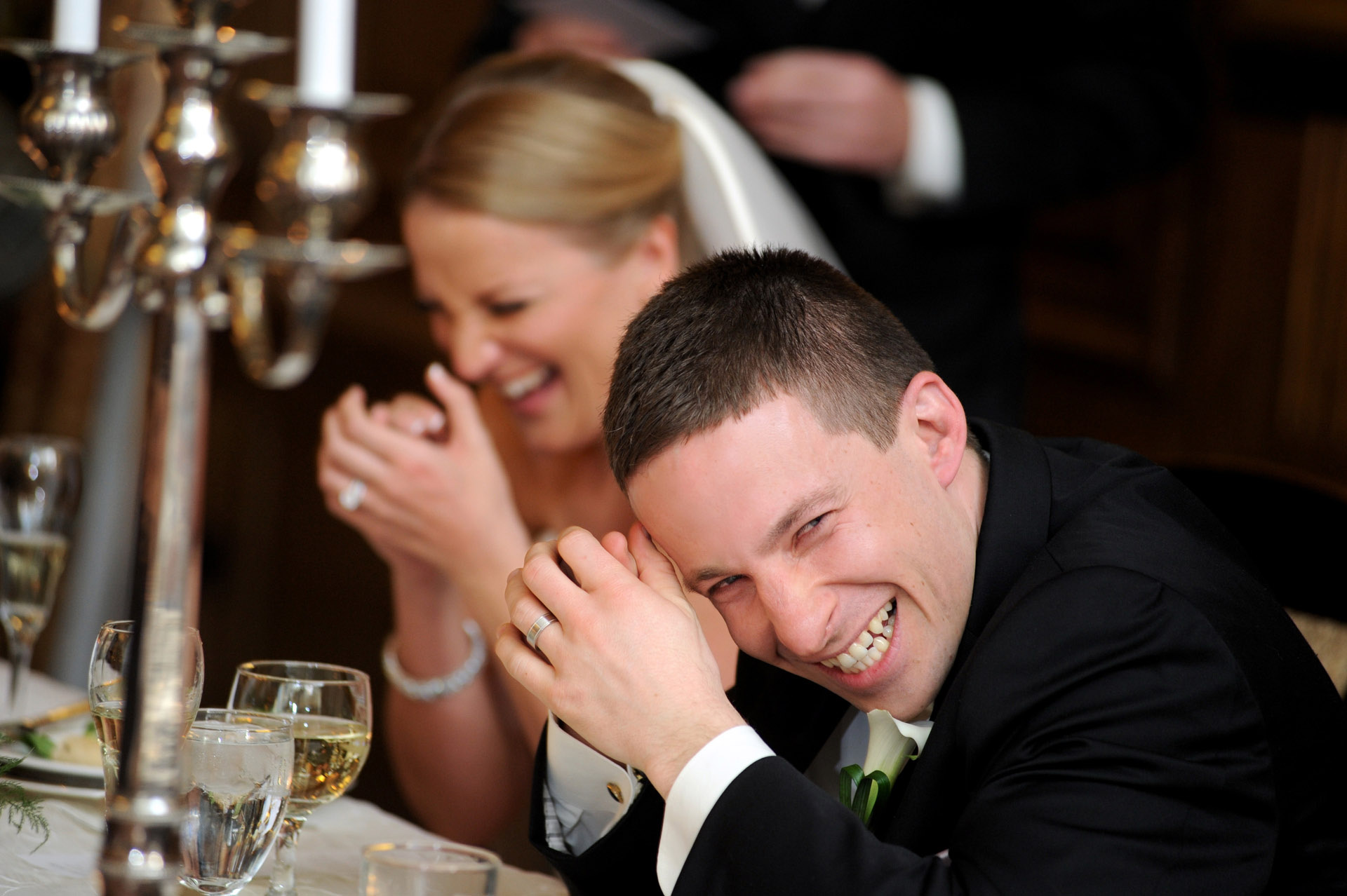 A windy winter wedding in Michigan features the bride and groom reacting to the toasts given during their wedding reception at the Detroit Athletic Club.