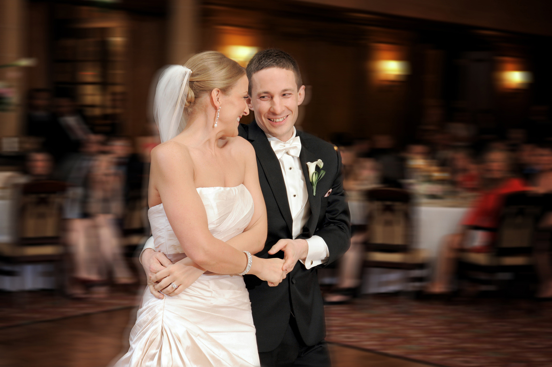 A windy winter wedding in Michigan features the bride and groom enjoying a spin on the dance floor at the Detroit Athletic Club.