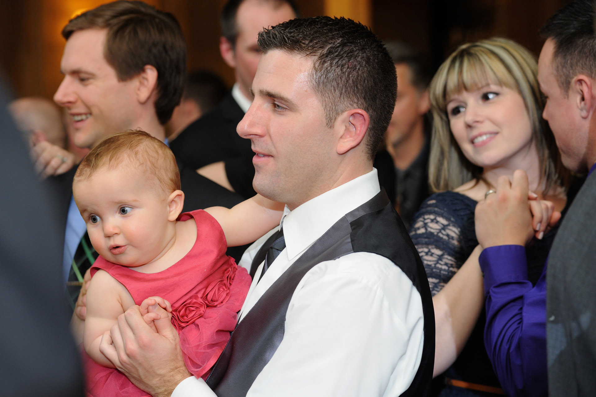 Michigan wedding in Detroit, Michigan, featured a photo of a groomsman dancing with his baby during the wedding reception at the Detroit Athletic Club.
