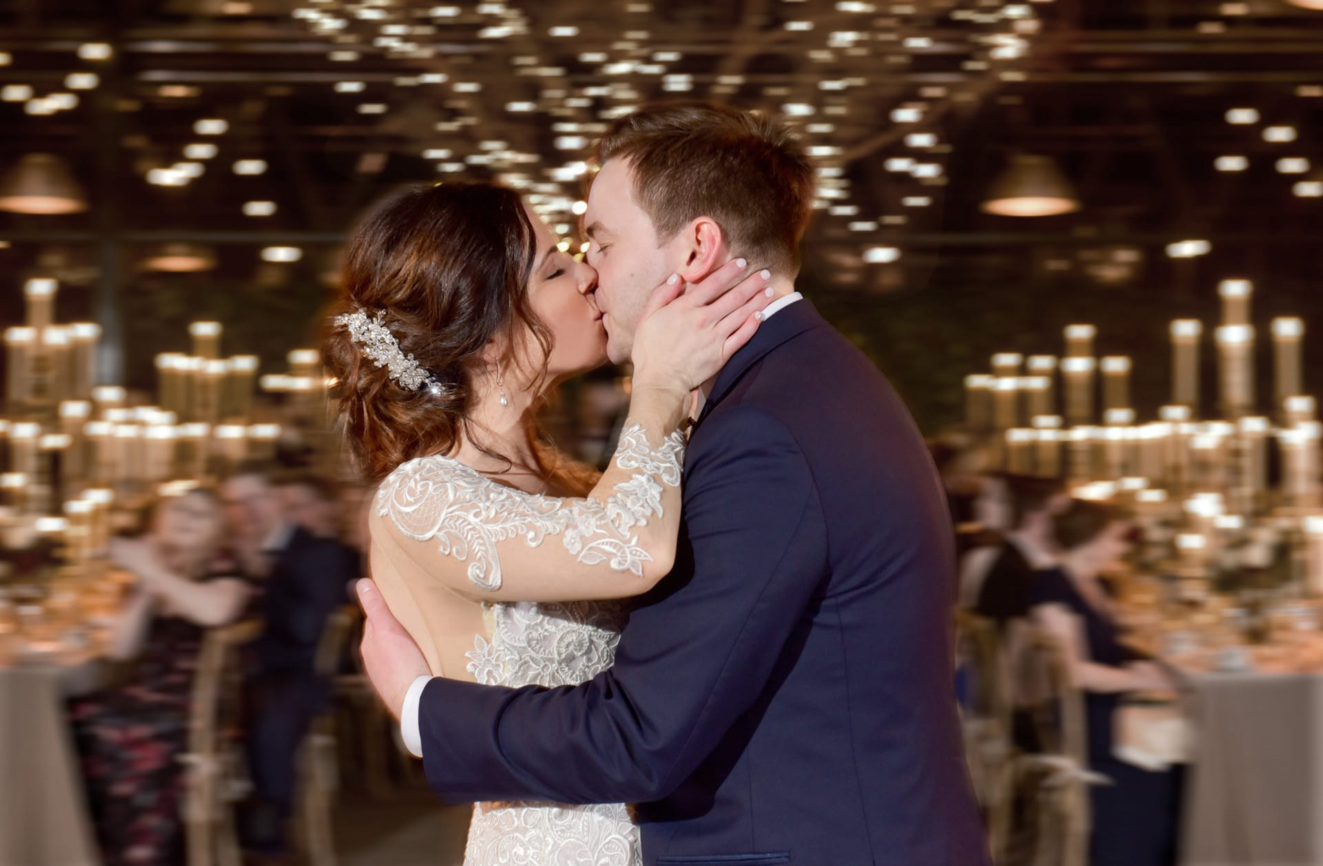 A couple kisses during their first dance at Planterra Conservatory in West Bloomfield, Michigan.