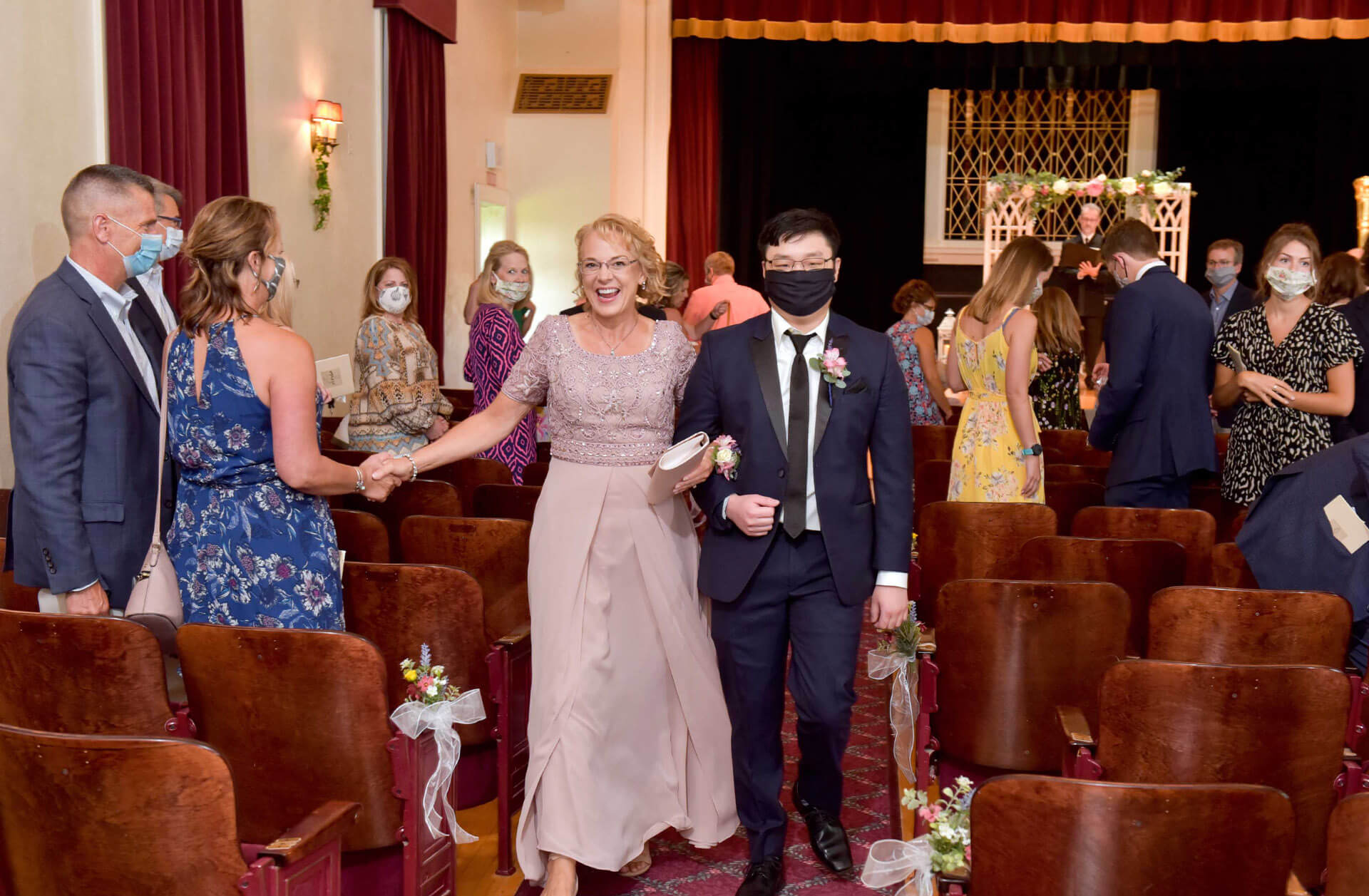 The mother of the bride is escorted down the aisle by her son after my first Covid wedding on a hot wedding day at Waldenwoods Resort in Howell, Michigan during the pandemic.