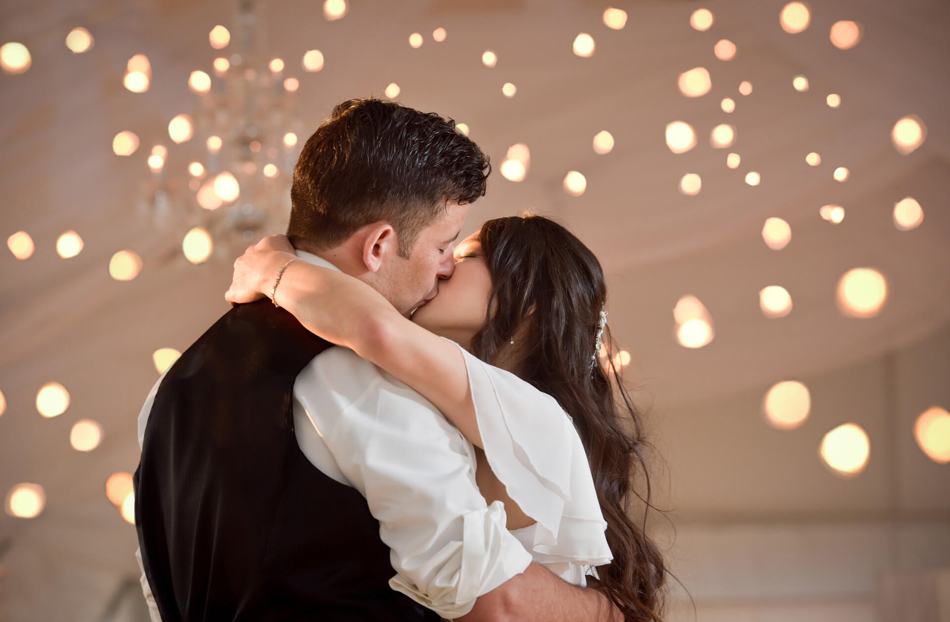 The groom and bride smooch during their first dance after a hot wedding day at Waldenwoods Resort in Howell, Michigan during the pandemic.