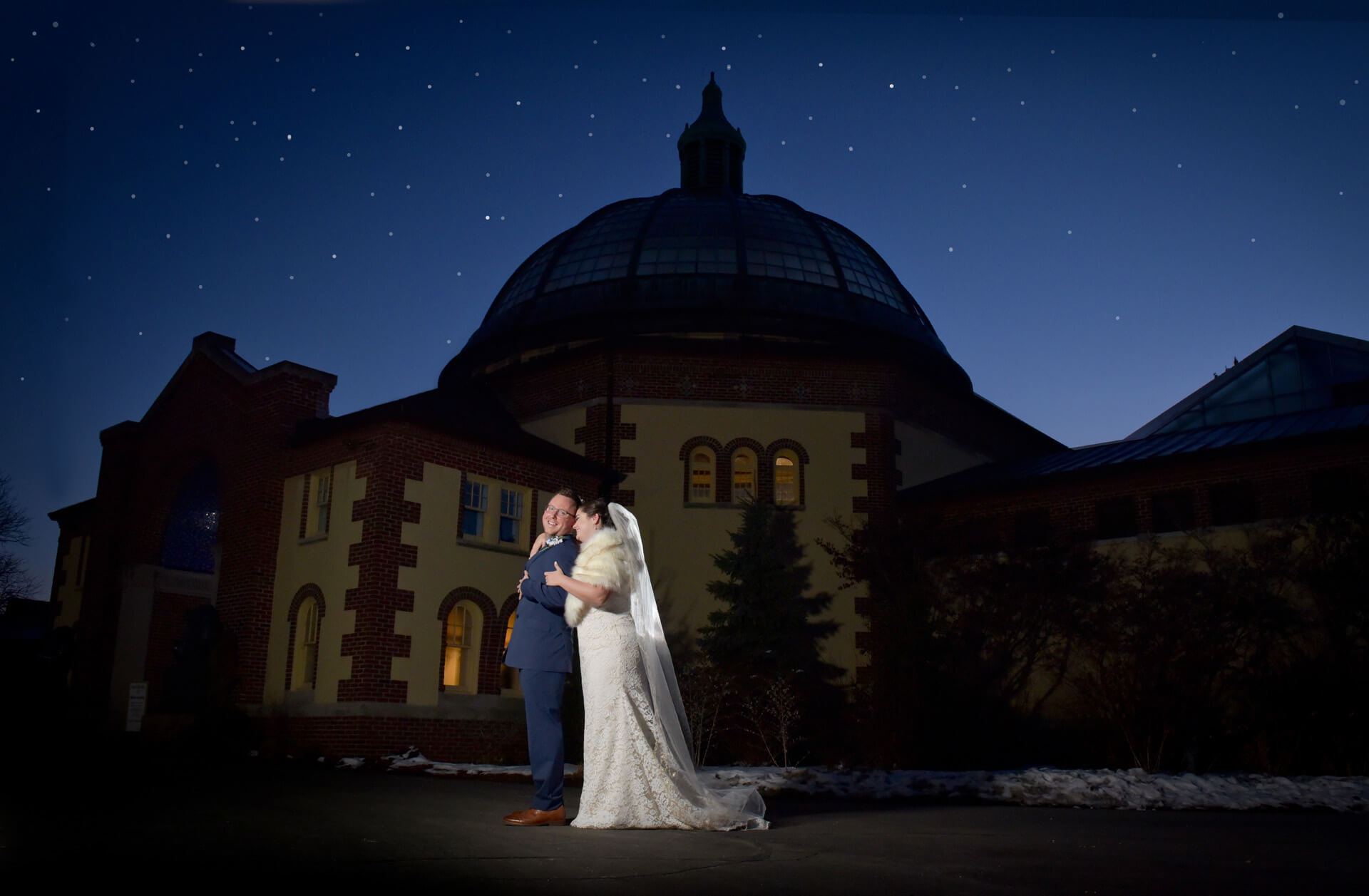 The groom and bride post at sundown at the Detroit Zoo in Royal Oak, Michigan where they had their wedding ceremony.