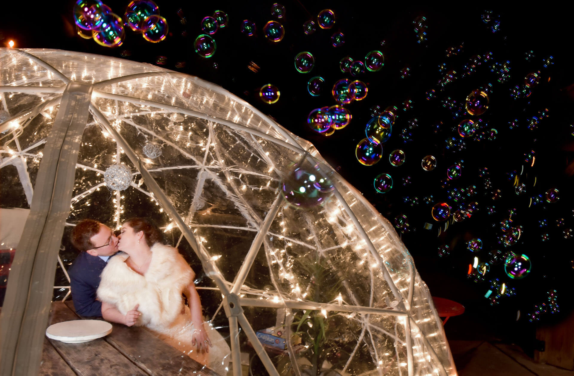 The bride and groom snuggle in an isolation igloo during their winter wedding reception at Detroit Fleat in Ferndale, Michigan.