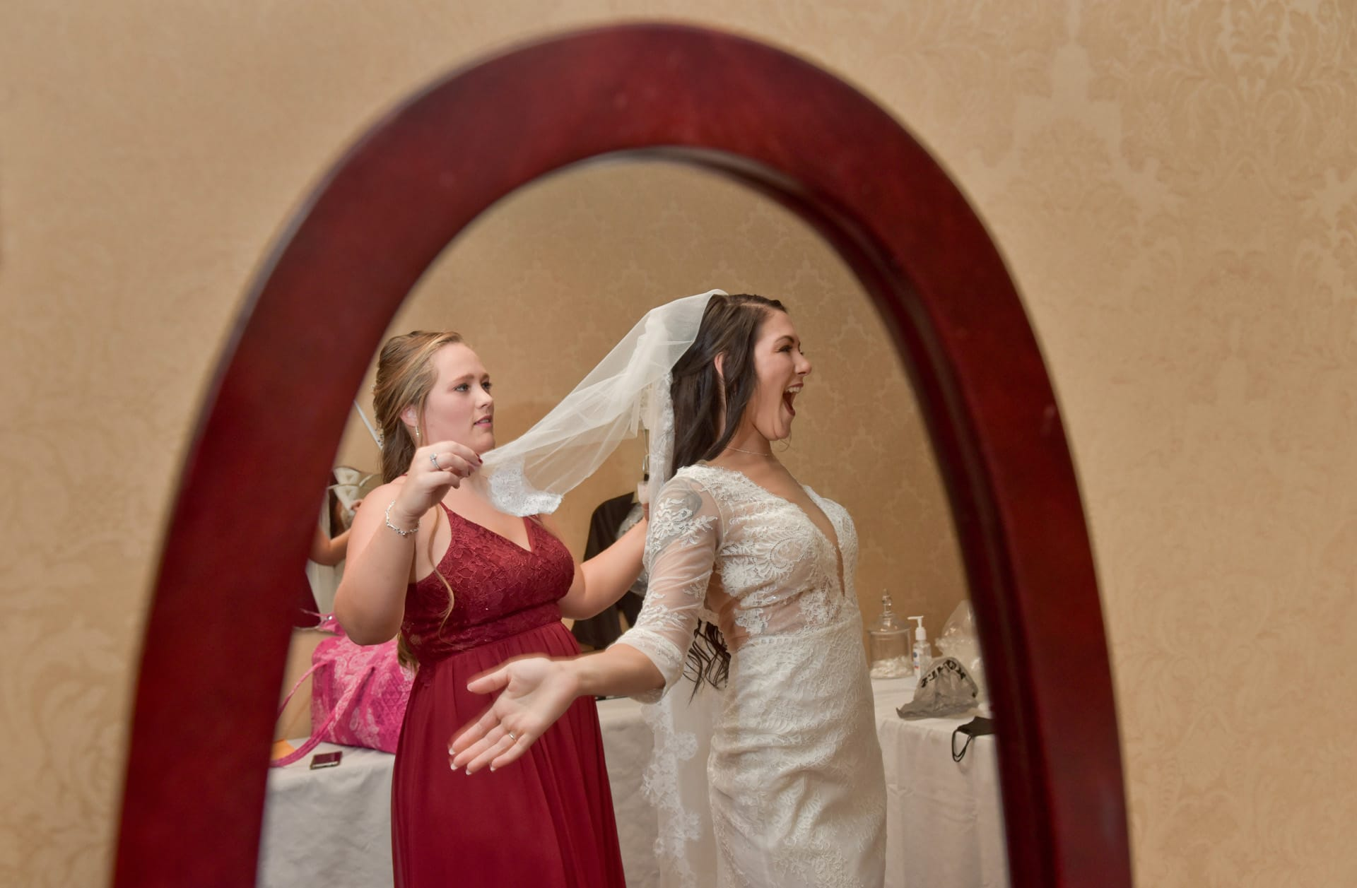 The bride sees herself for the first time in the mirror in her dress at her wedding downriver, Michigan.