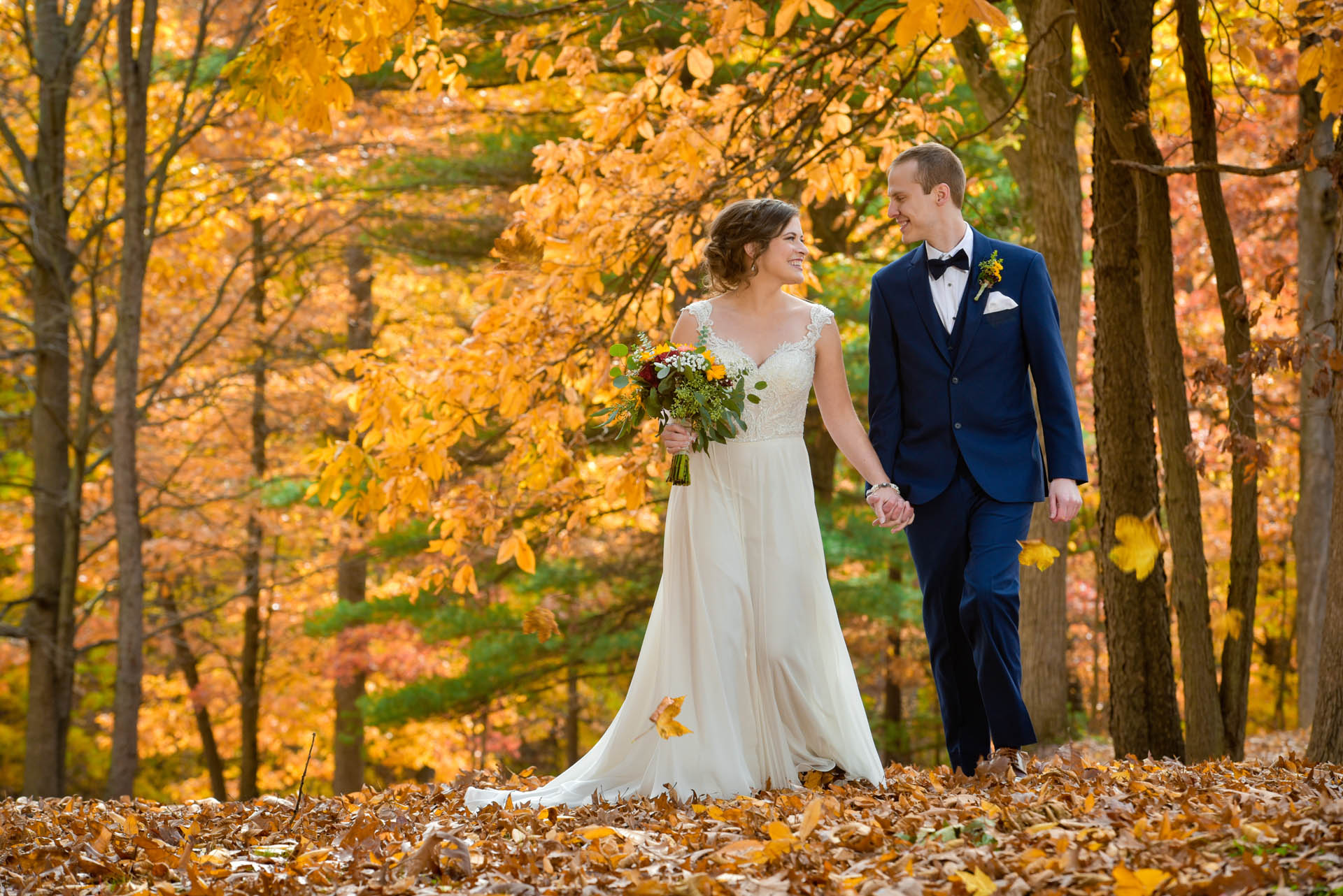 The bride and groom stroll through the leaves in the fall on their wedding day at Waldenwoods Resort in Howell, Michigan.
