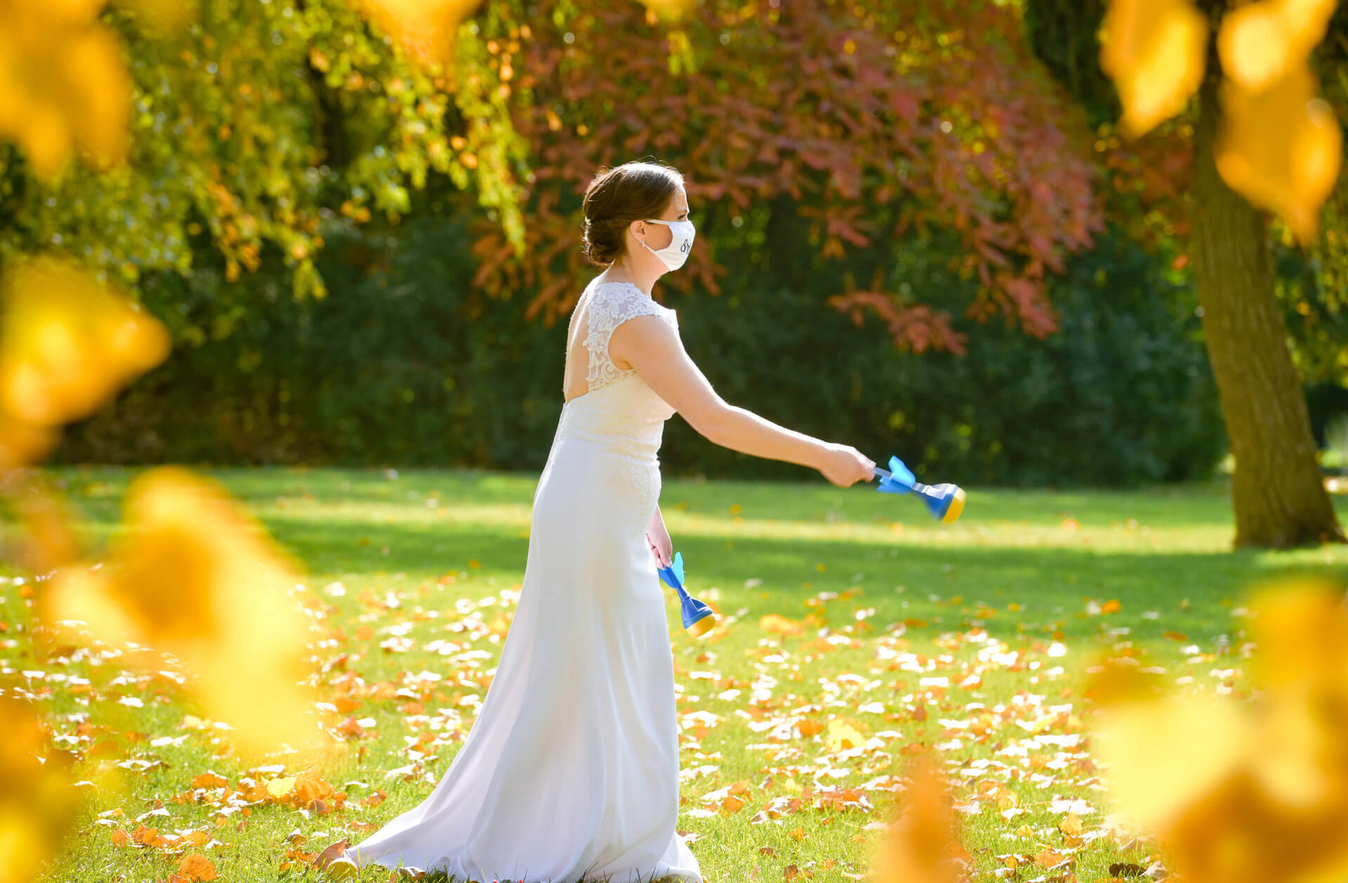 The bride plays lawn darts during her small family wedding at home in Farmington, Michigan during the pandemic.