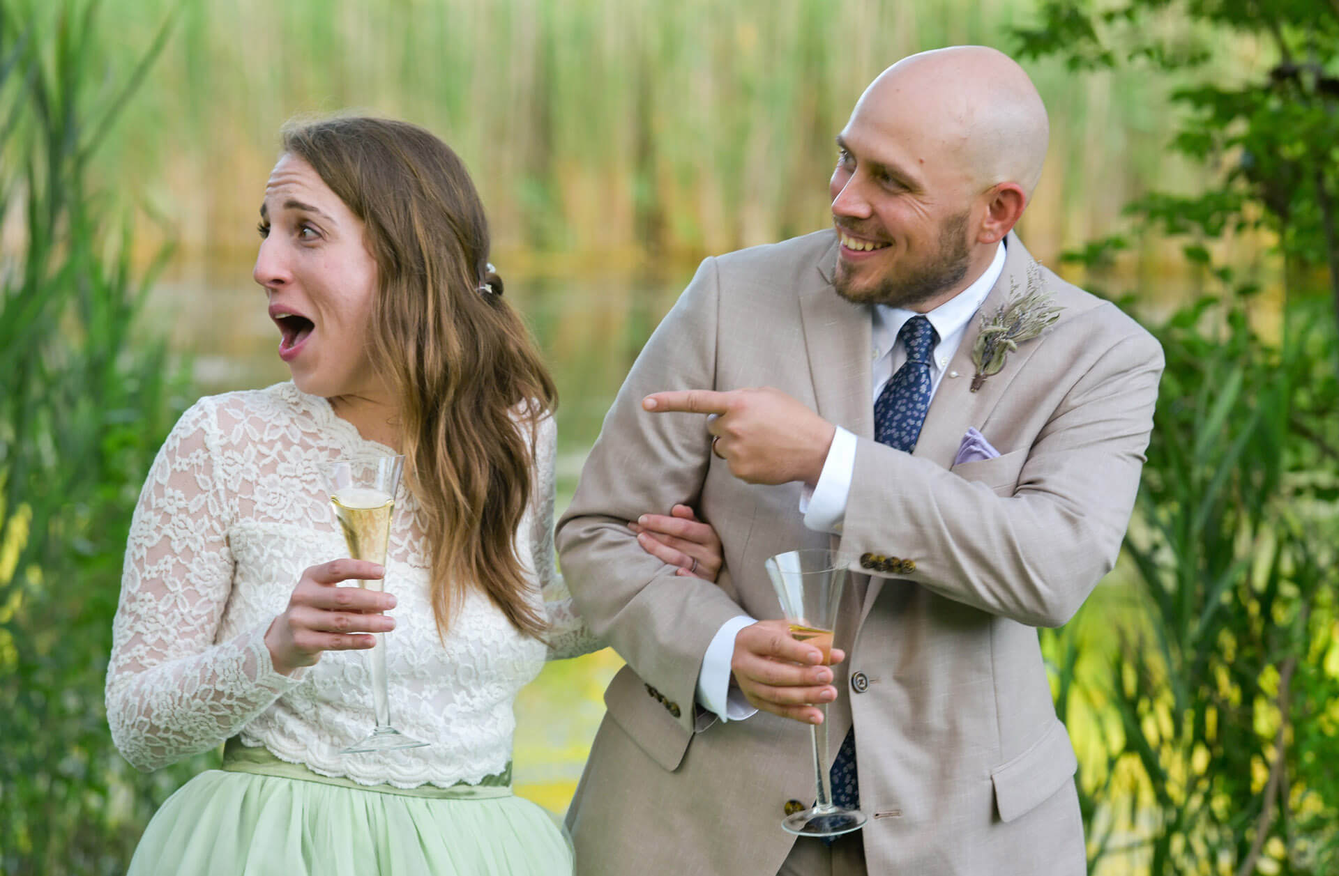 The bride and groom laugh during the toasts during their super small wedding in their Ann Arbor, Michigan backyard during the pandemic.