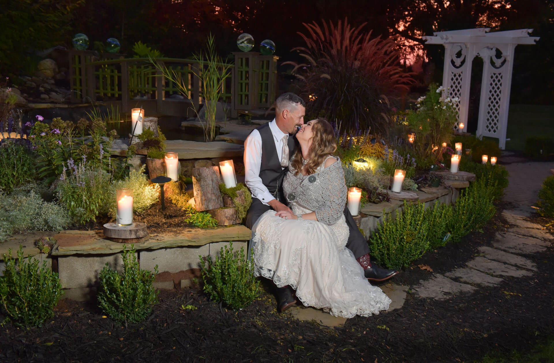 The bride and groom snuggle at the end of their backyard wedding after sunset near Metro Detroit, Michigan.