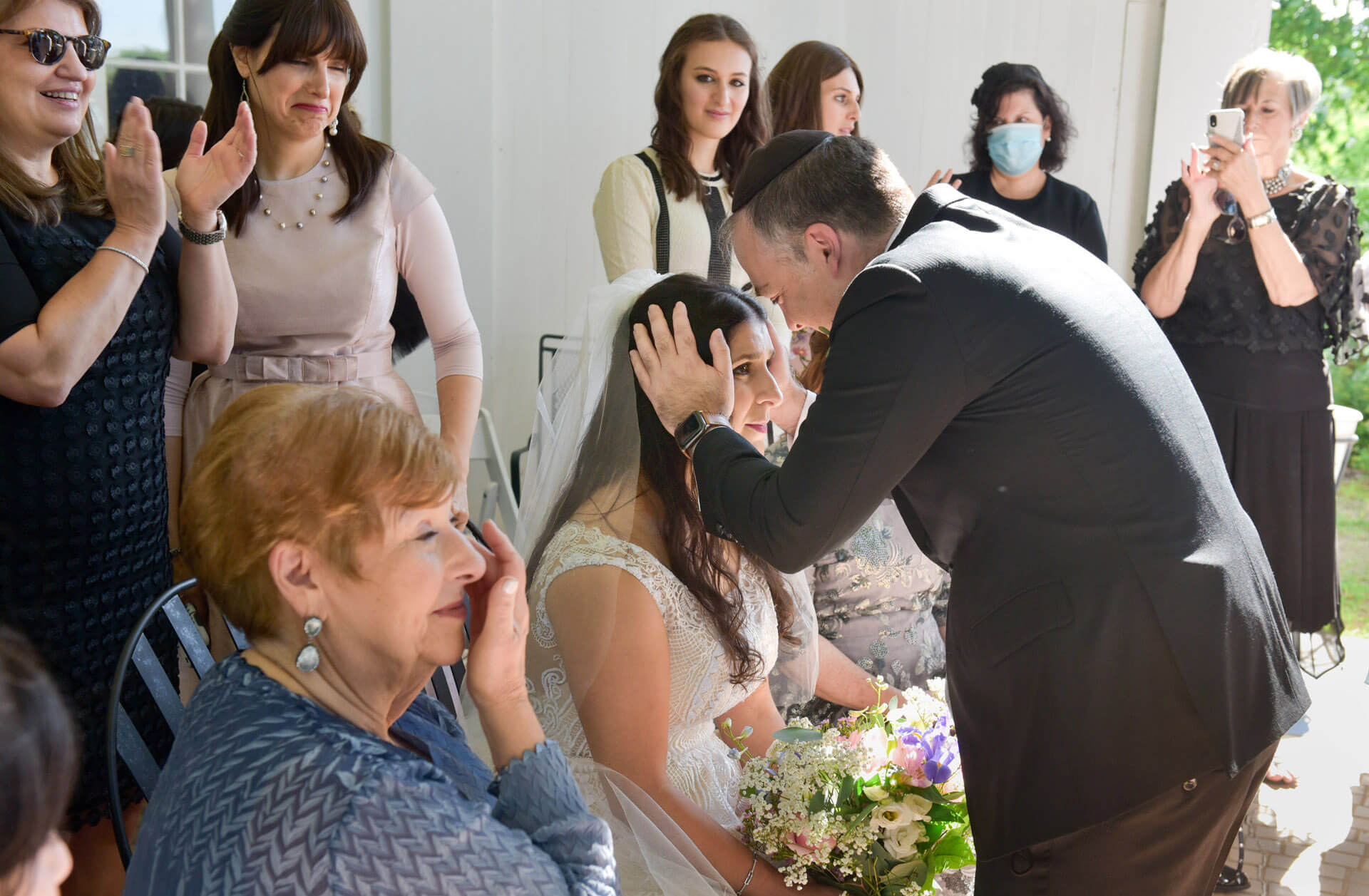 The bride receives a blessing from her brother during her orthodox Jewish wedding held during the pandemic at Waldenwoods Resort in Howell, Michigan.