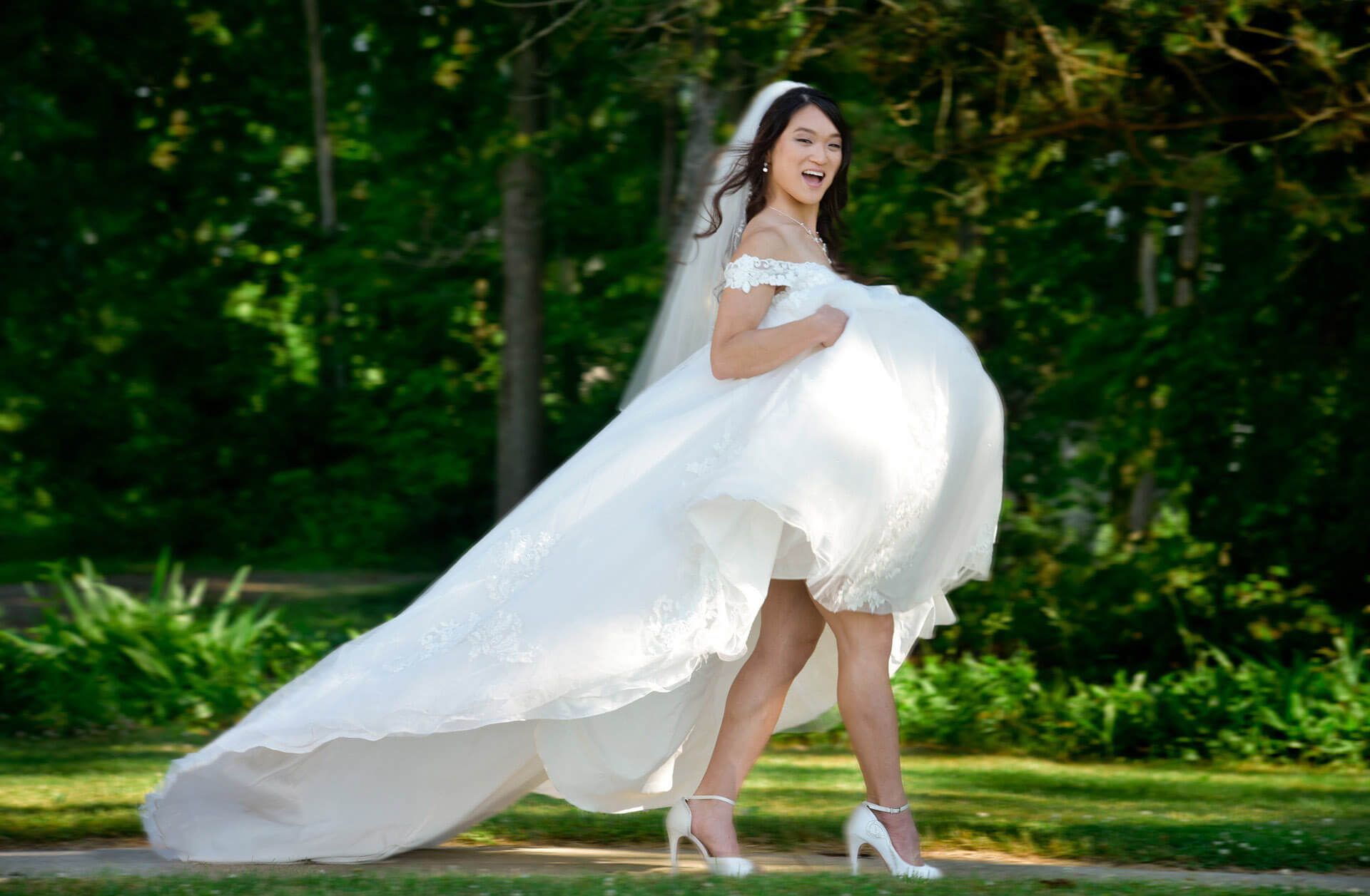 The bride hikes up her wedding dress as she heads out on a hot wedding day at Waldenwoods Resort in Howell, Michigan.