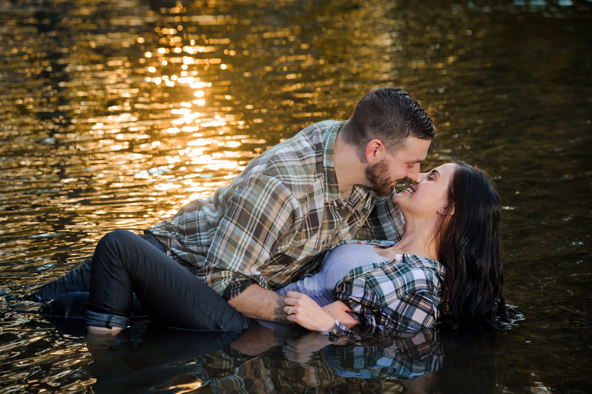 Best Detroit engagement photographer's fun and candid engagement features clients super hot photo of a couple in the water in Rochester, Michigan.
