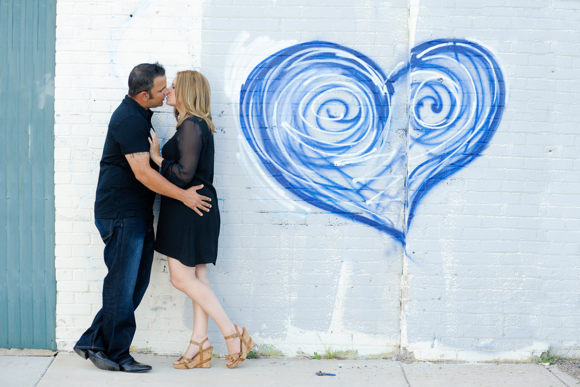 Best Detroit engagement photographer's fun and candid engagement photos of a Michigan newly engaged couple with ever changing graffiti art in Detroit's Eastern Market.