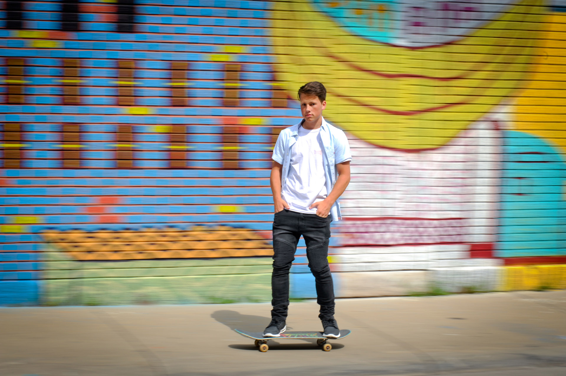 Best Detroit senior photographer's high school senior picture of a Bishop Foley senior photo taken on his skateboard in front of graffiti art from downtown Detroit, Michigan.