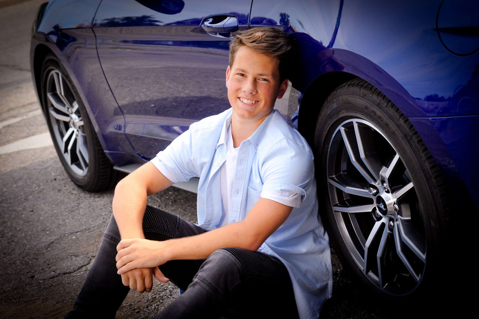 Best Detroit senior photographer's high school senior picture of a Bishop Foley senior on next to his beloved Mustang car in downtown Detroit, Michigan.