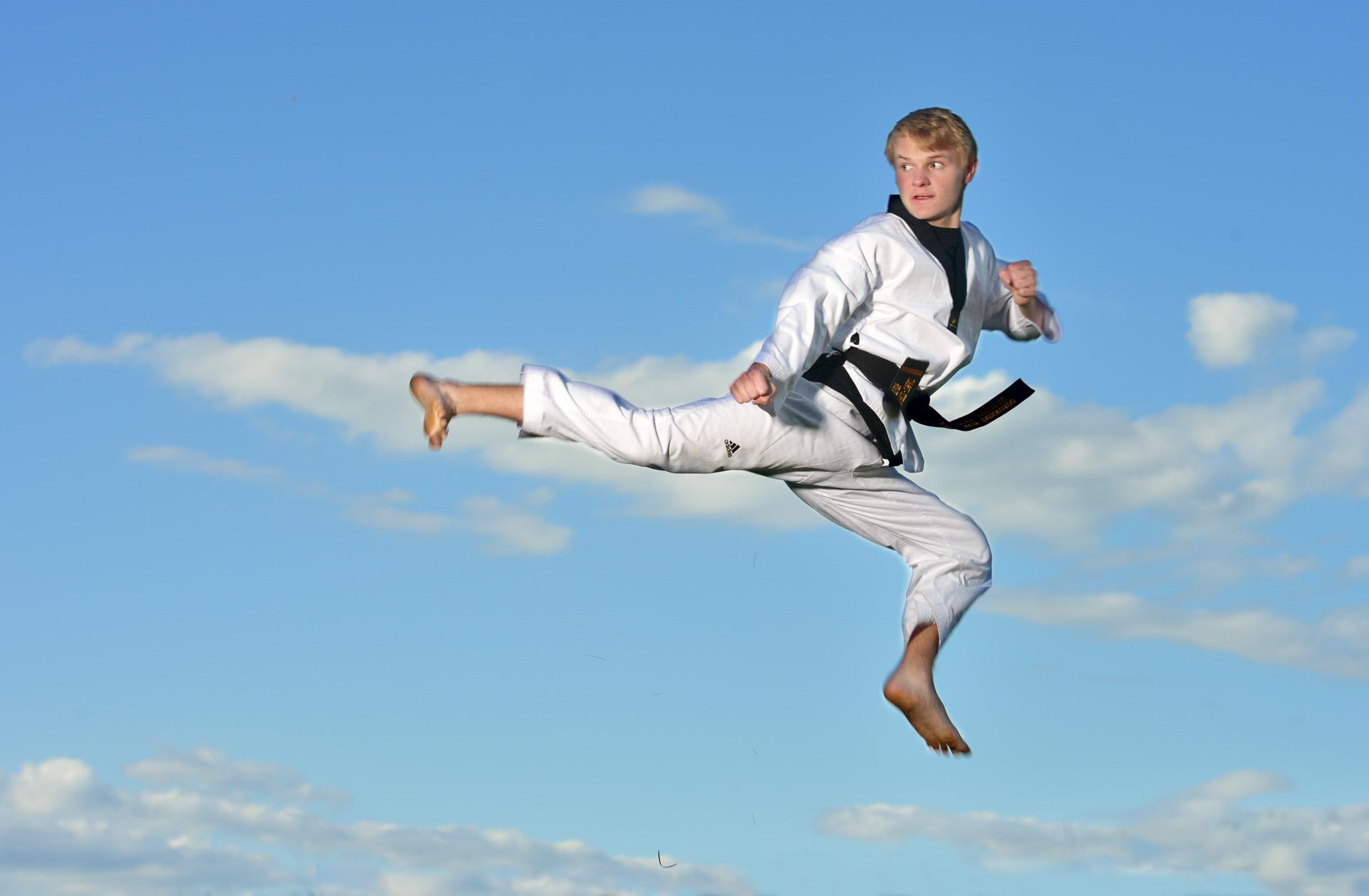 Troy High School student shows off his taekwondo skills on a hilltop in Birmingham, Michigan for a dynamic, powerful senior photo.
