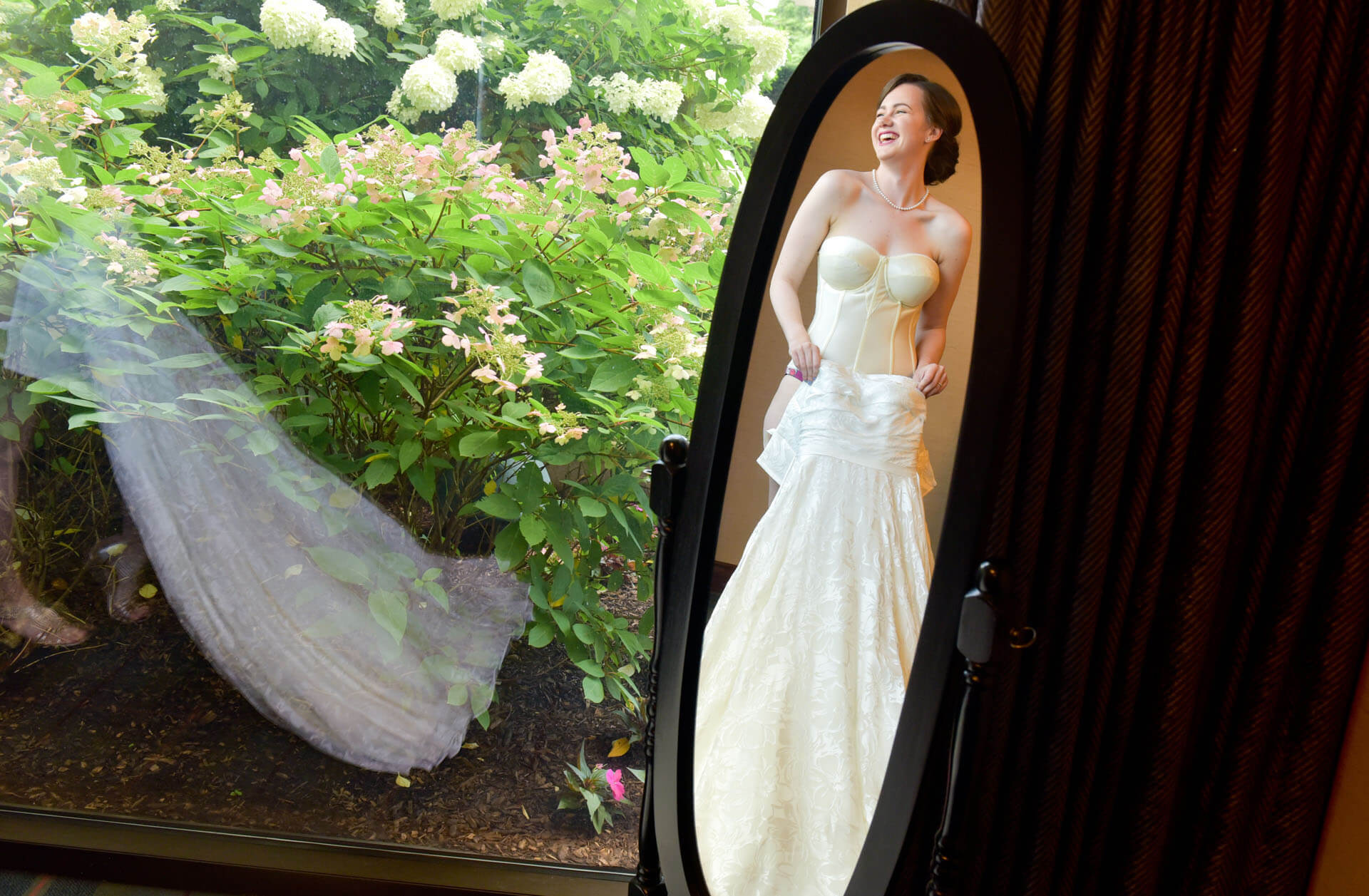 A bride gets dressed in the mirror in Ann Arbor, Michigan.