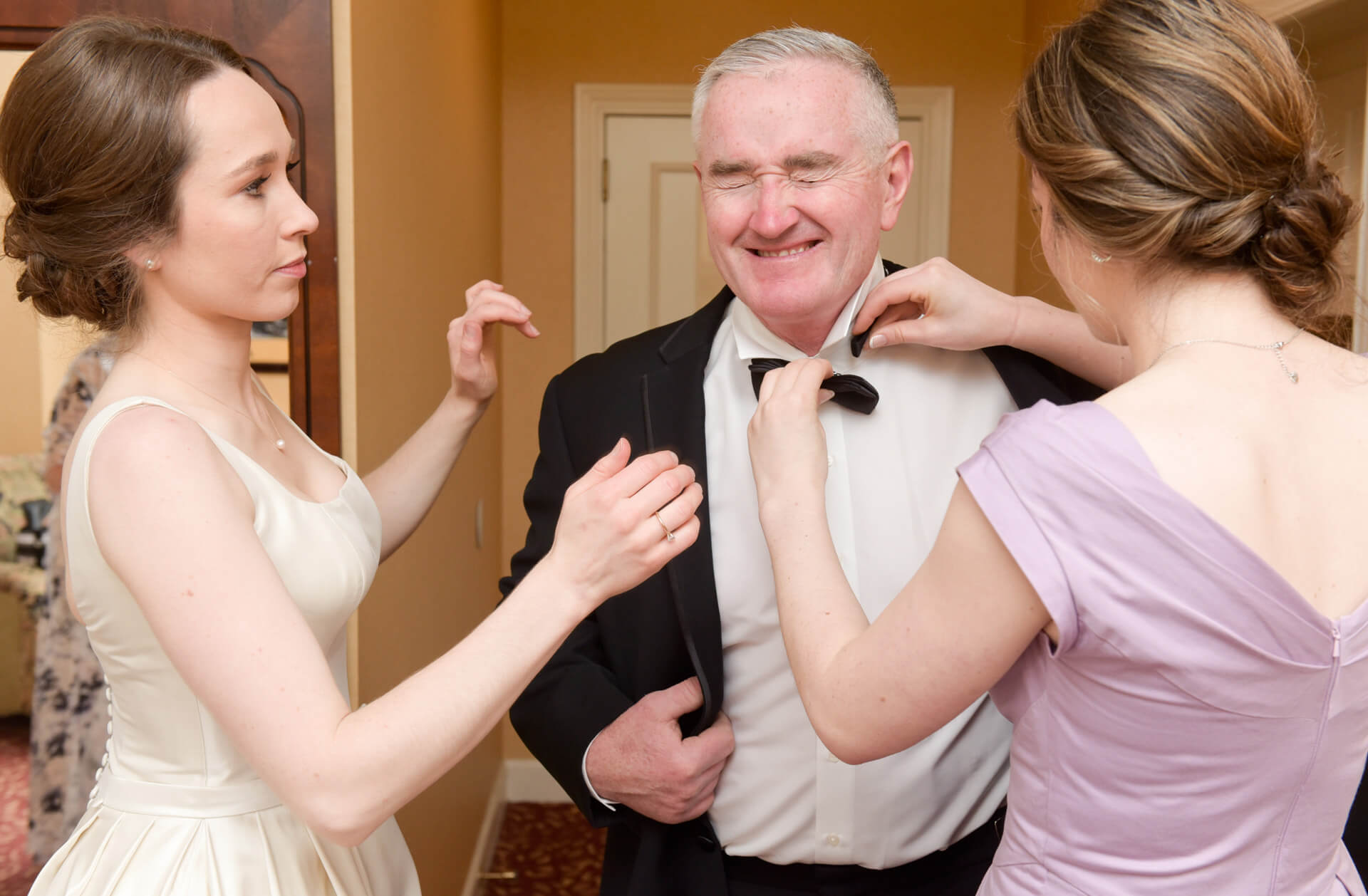 Candid wedding photography showing the bride and sister trying to tightened her father's tie at the Dearborn Inn wedding in Dearborn, Michigan.
