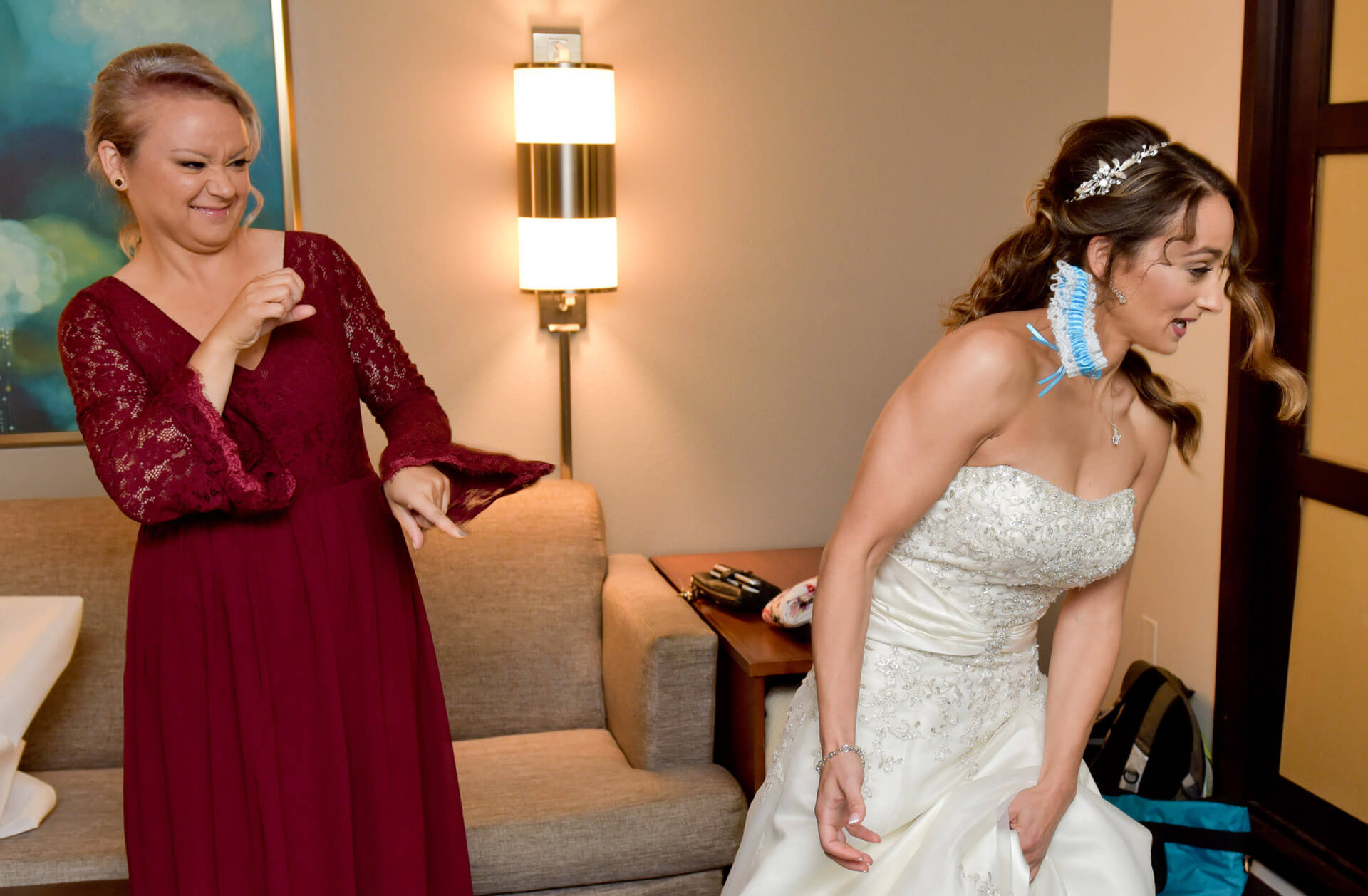 Fun, candid wedding candid moments like this bridesmaid snapping the garter at the bride, catching her totally unaware in Detroit, Michigan!
