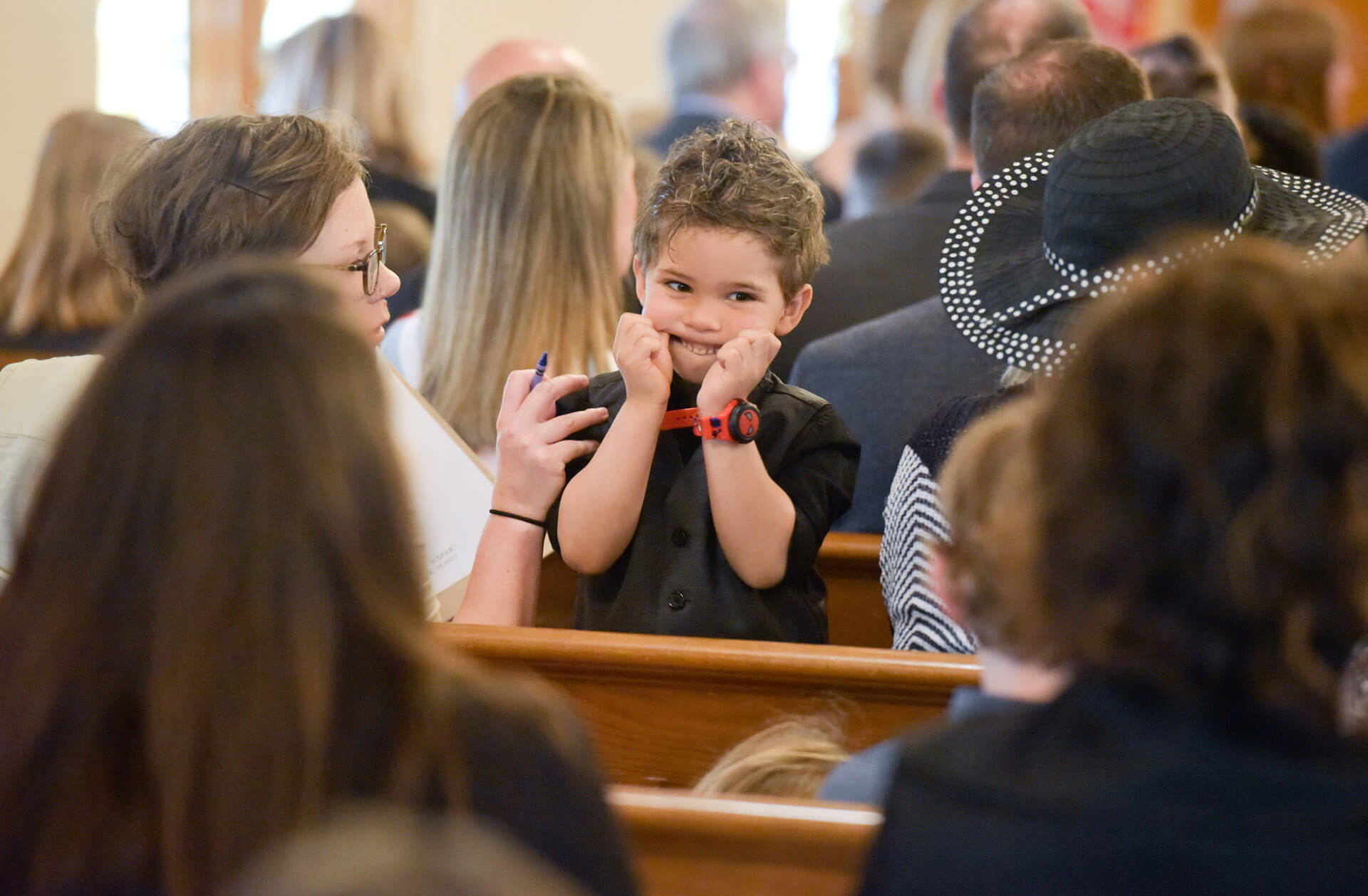 A bored young wedding guest entertains himself by making faces during a Catholic wedding service in Troy, Michigan.