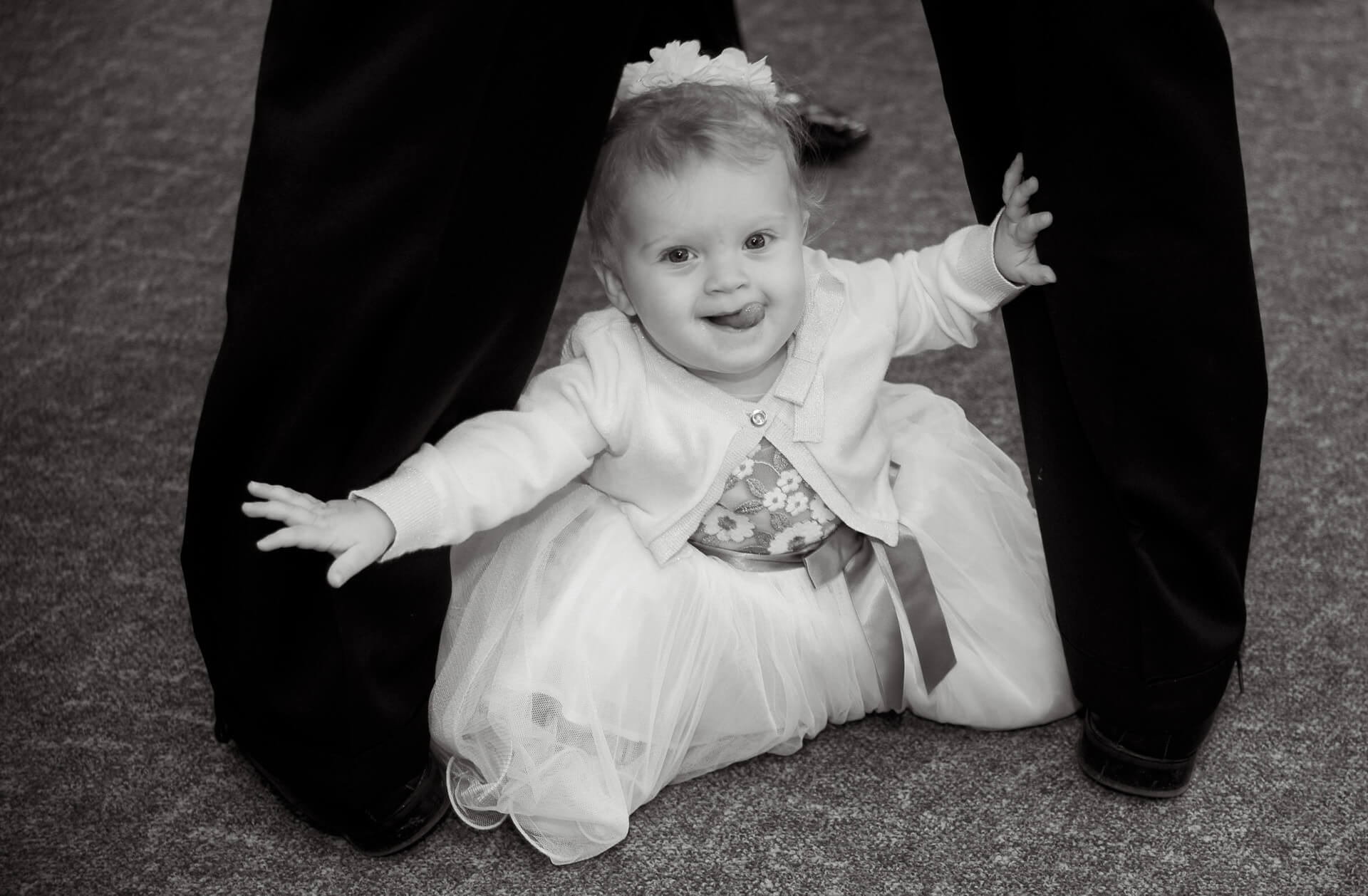 Candid wedding photography showing a baby flower girl playing between her father's legs during a Detroit, Michigan wedding.