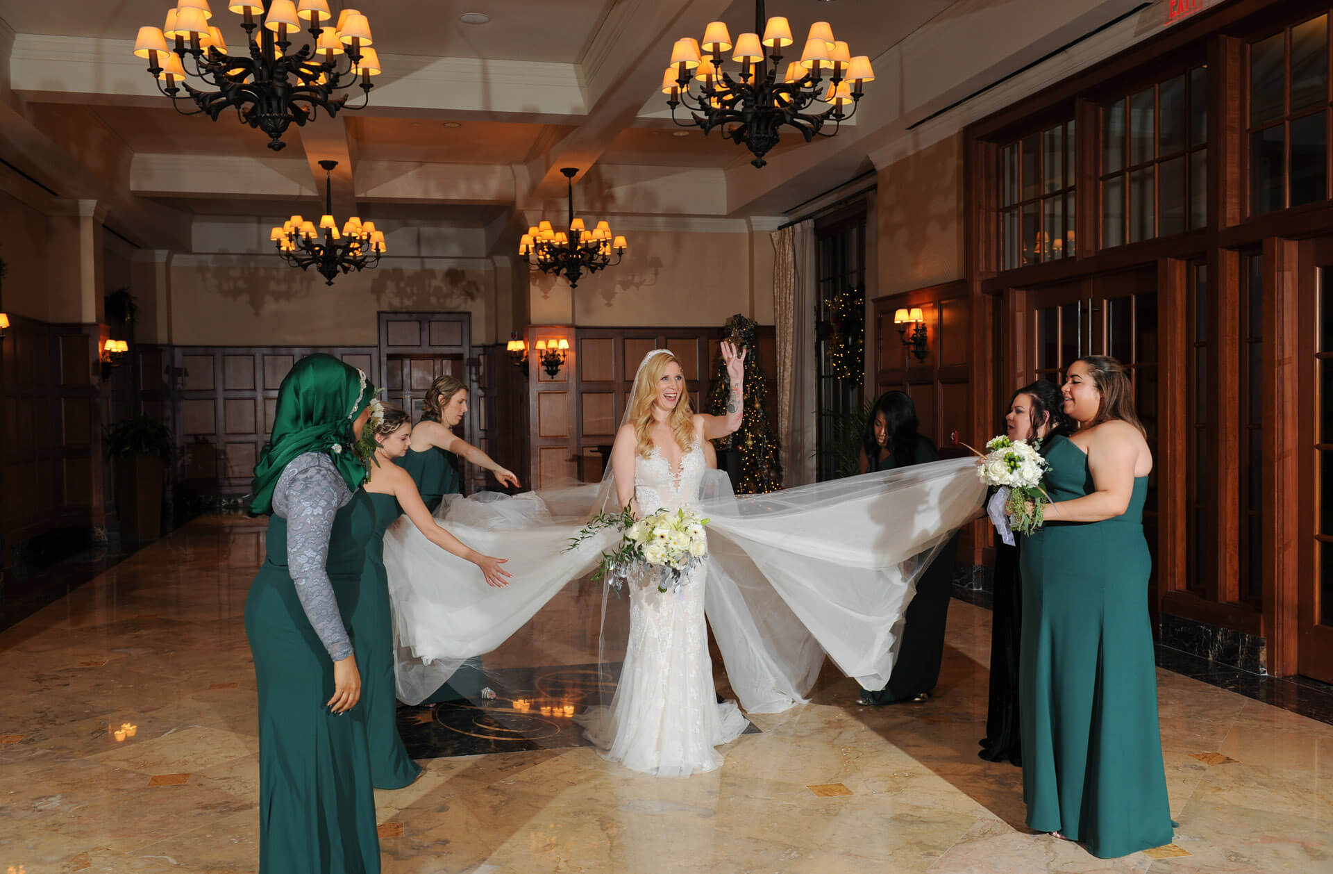 Candid wedding photography showing the bride waving to guests while bridesmaids adjust her dress before a wedding at the Royal Park Hotel in Rochester, Michigan.