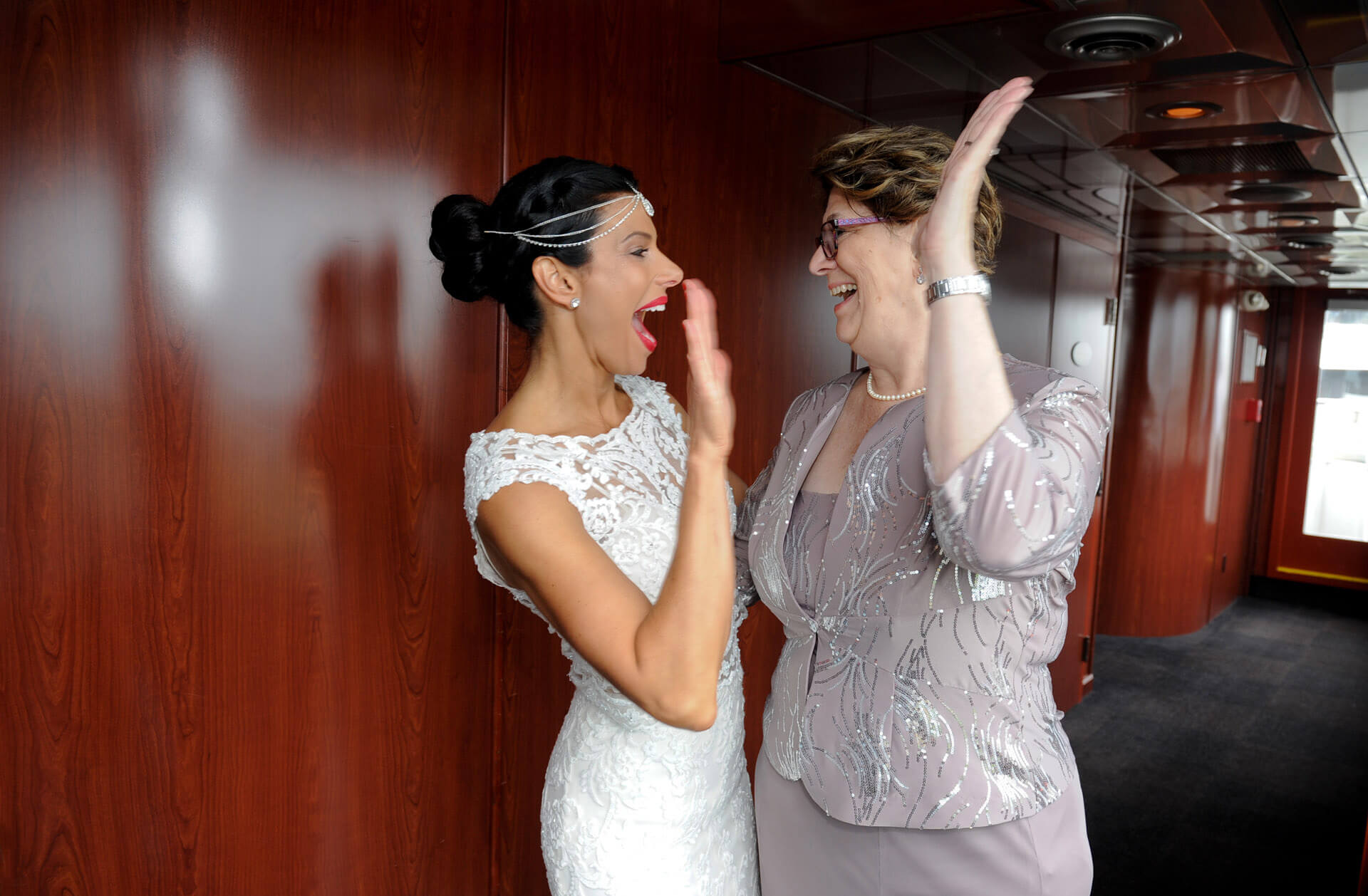 Candid wedding photography showing bride high giving her new mother in law on board the Ovation Yacht in Detroit, Michigan.
