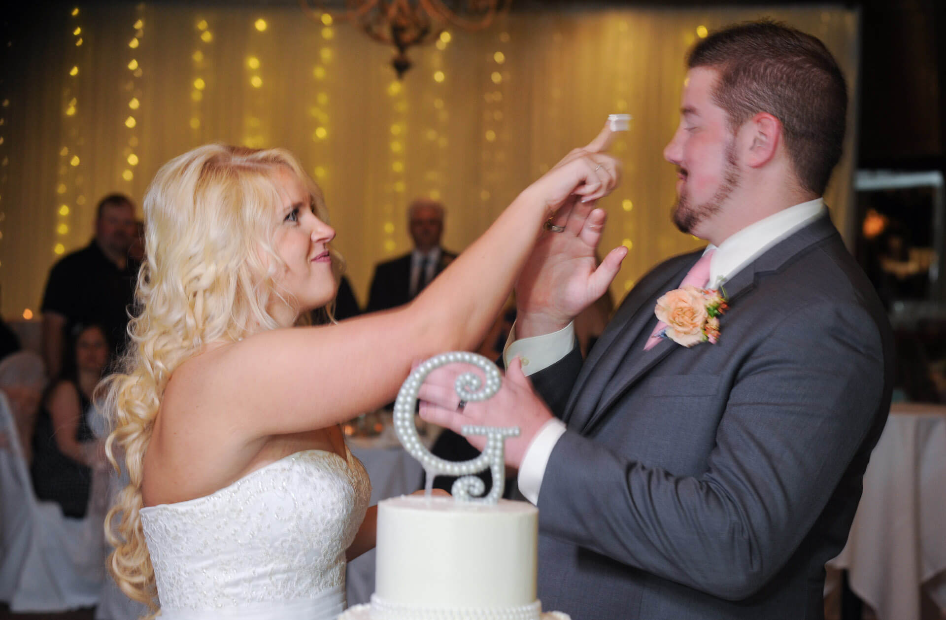 Candid wedding photography showing a bride about to smash cake in her groom's face at their metro Detroit wedding.