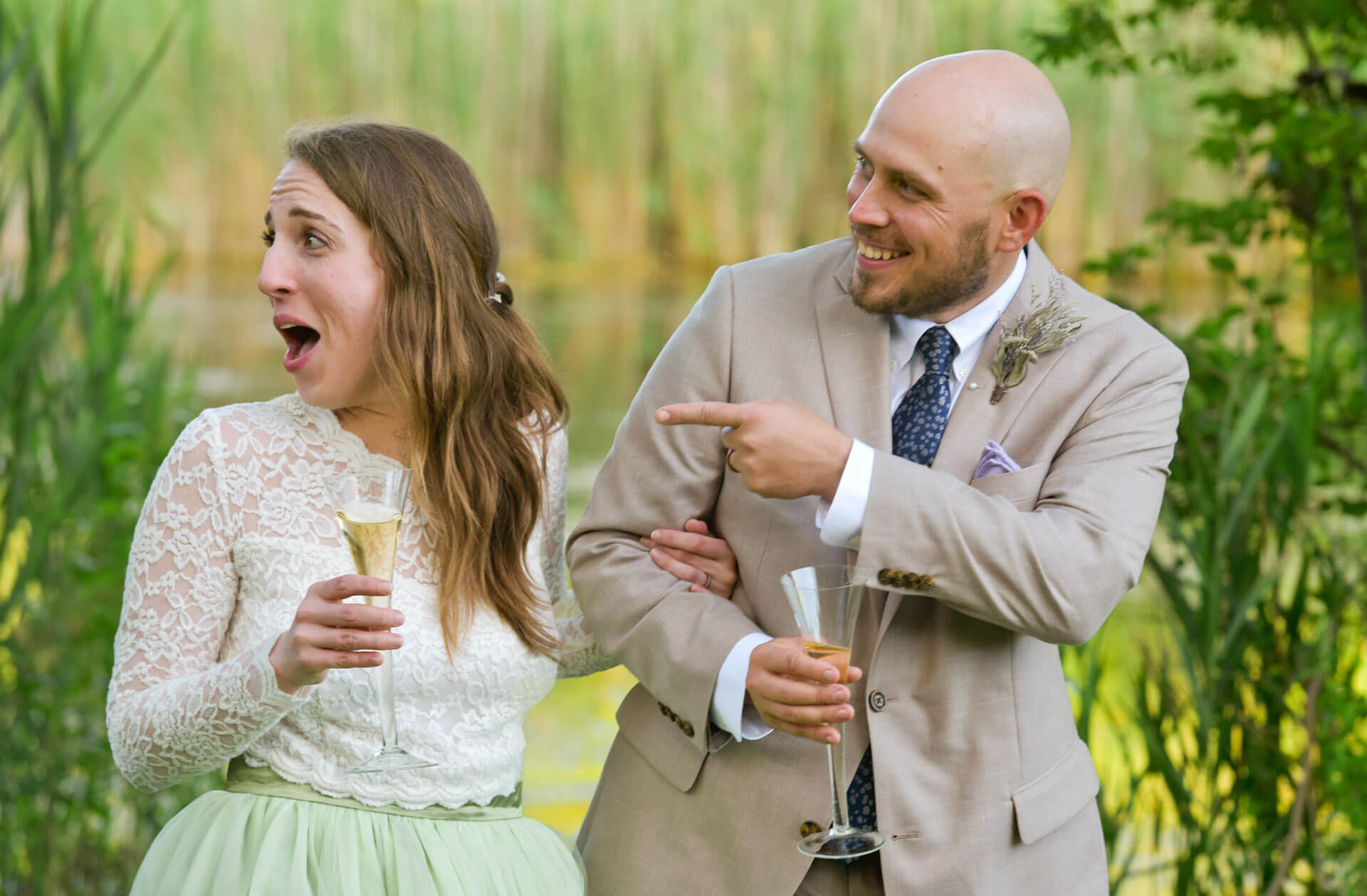 Candid wedding photography showing the bride and groom laughing during their toast in their backyard wedding in Ann Arbor, Michigan.