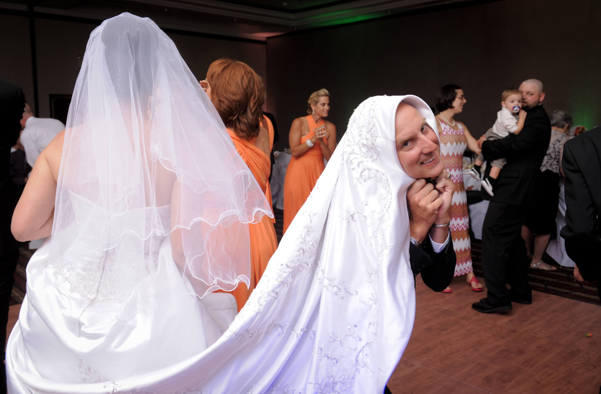 Candid wedding photography showing a groomsman playing with the bride's train during a wedding reception in downtown Detroit, Michigan.