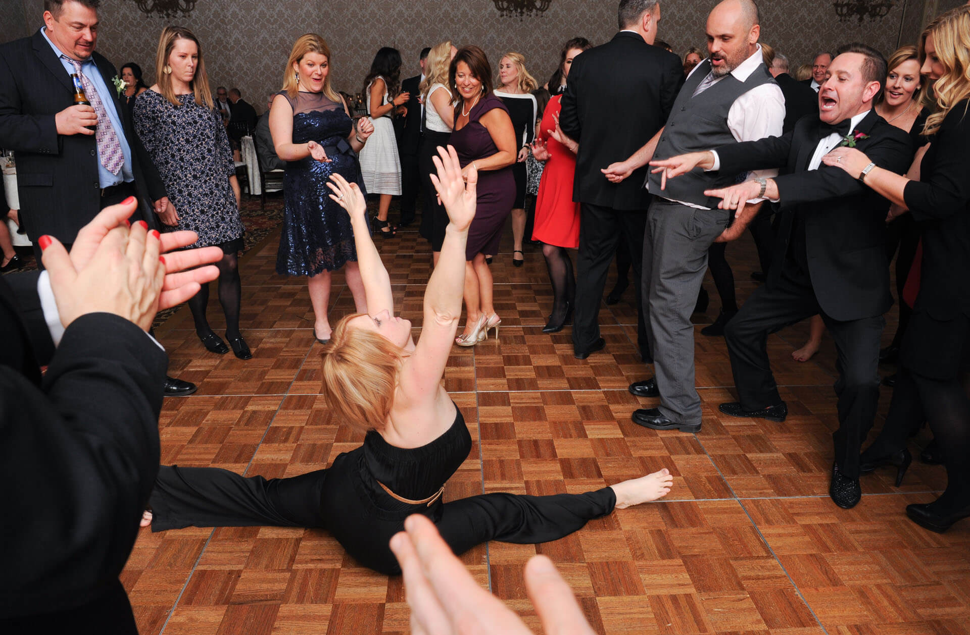 Candid wedding photography showing a guest doing the splits during a dance at a wedding reception at the Royal Park Hotel in Rochester, Michigan.