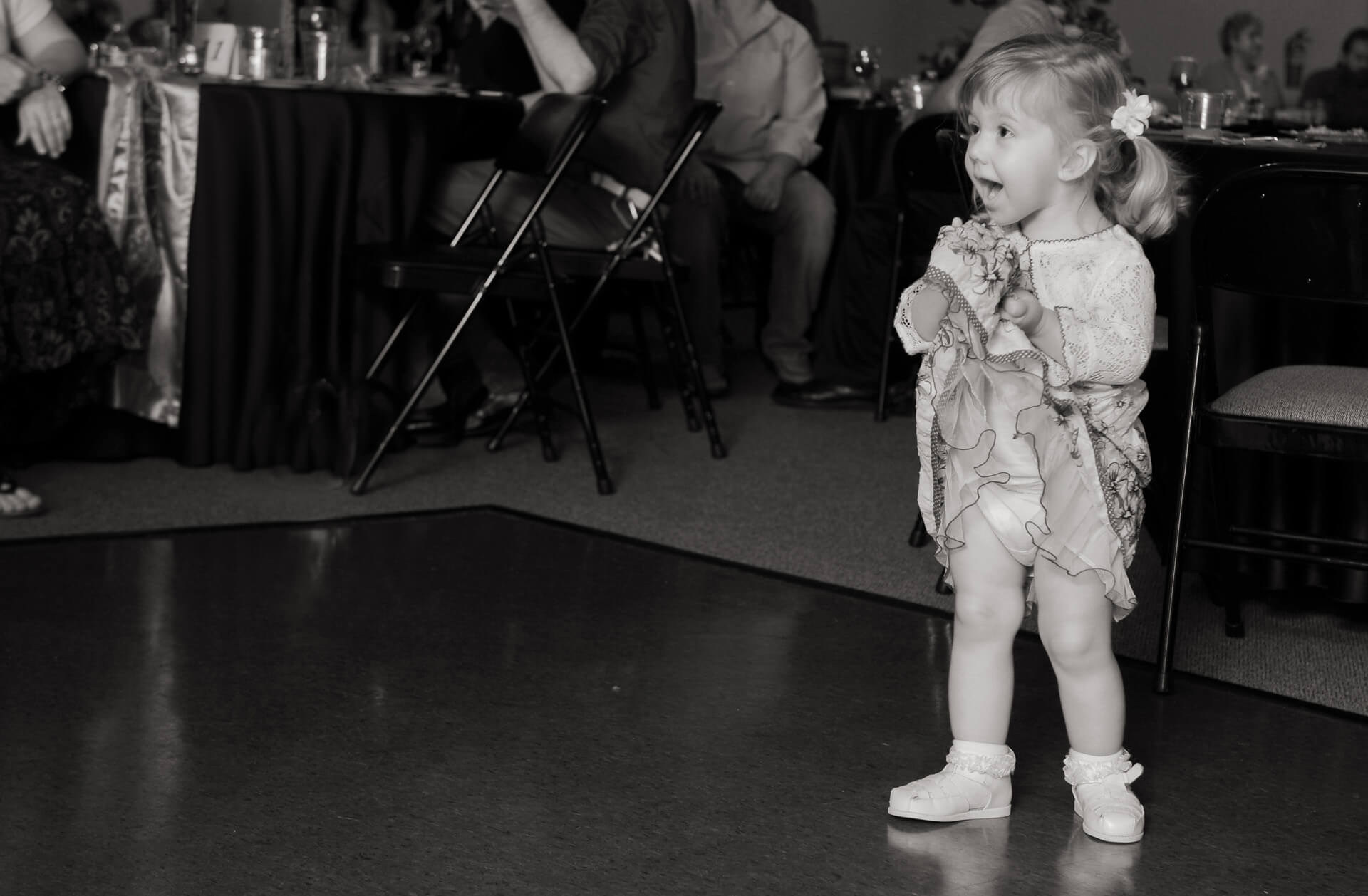 Candid wedding photography showing a little guest at a metro Detroit, Michigan lifting up her skirt for all to see at the wedding reception.