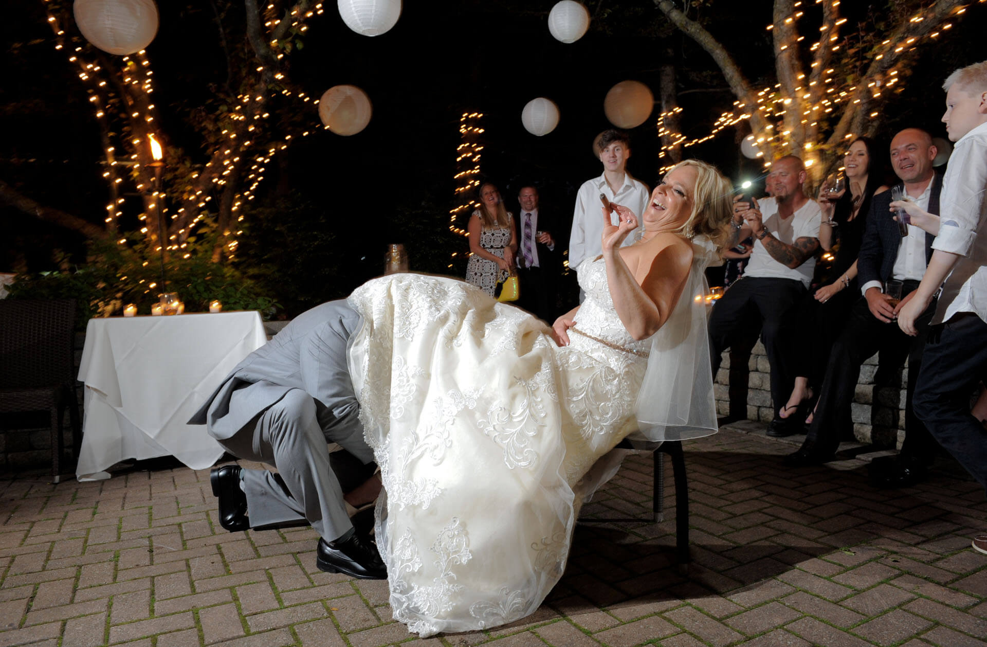 Candid wedding photography showing the bride laughing while the groom tries to find the garter at their outdoor Cafe Cortina wedding reception in Farmington, Michigan.