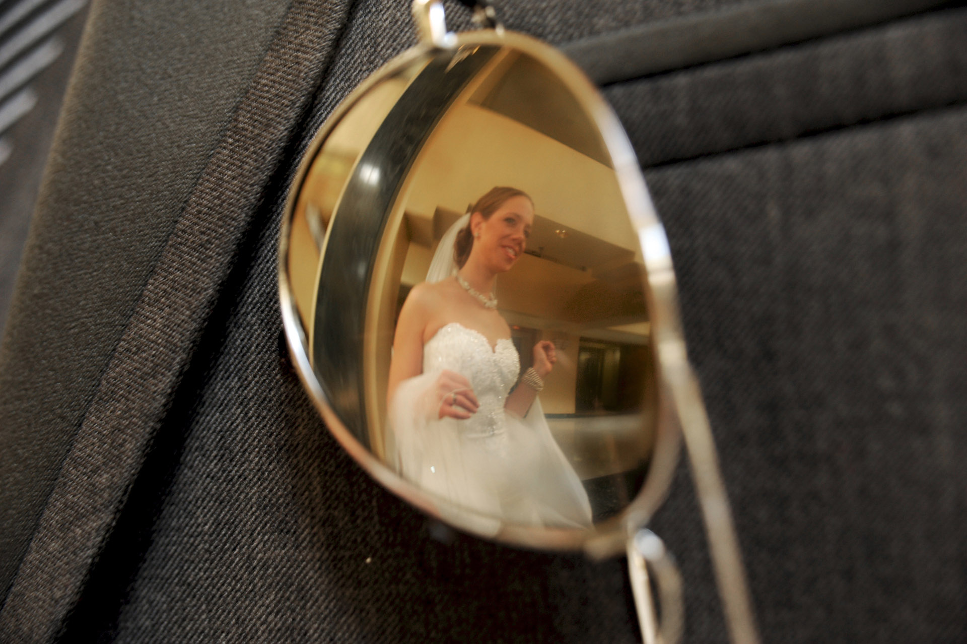 Detroit, Michigan wedding photographer shows the bride reflected in the groom's sunglasses after their first look at the Colony Club in Detroit, Michigan.