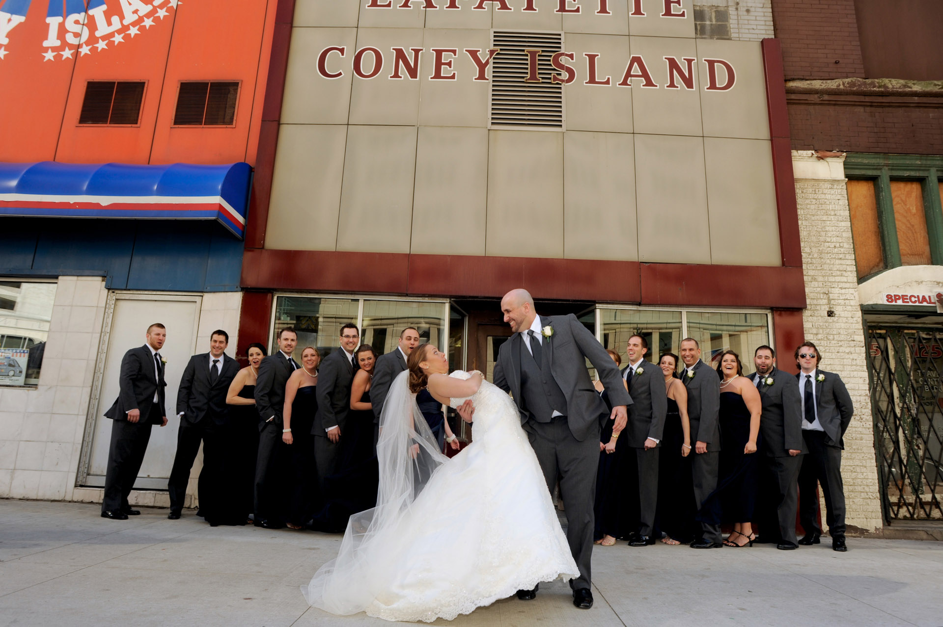 Detroit, Michigan wedding photographer's photo of the wedding party in front of Lafayette Coney Island in Detroit, Michigan when the bride grabs her dress fearing she's exposing herself. She wasn't!