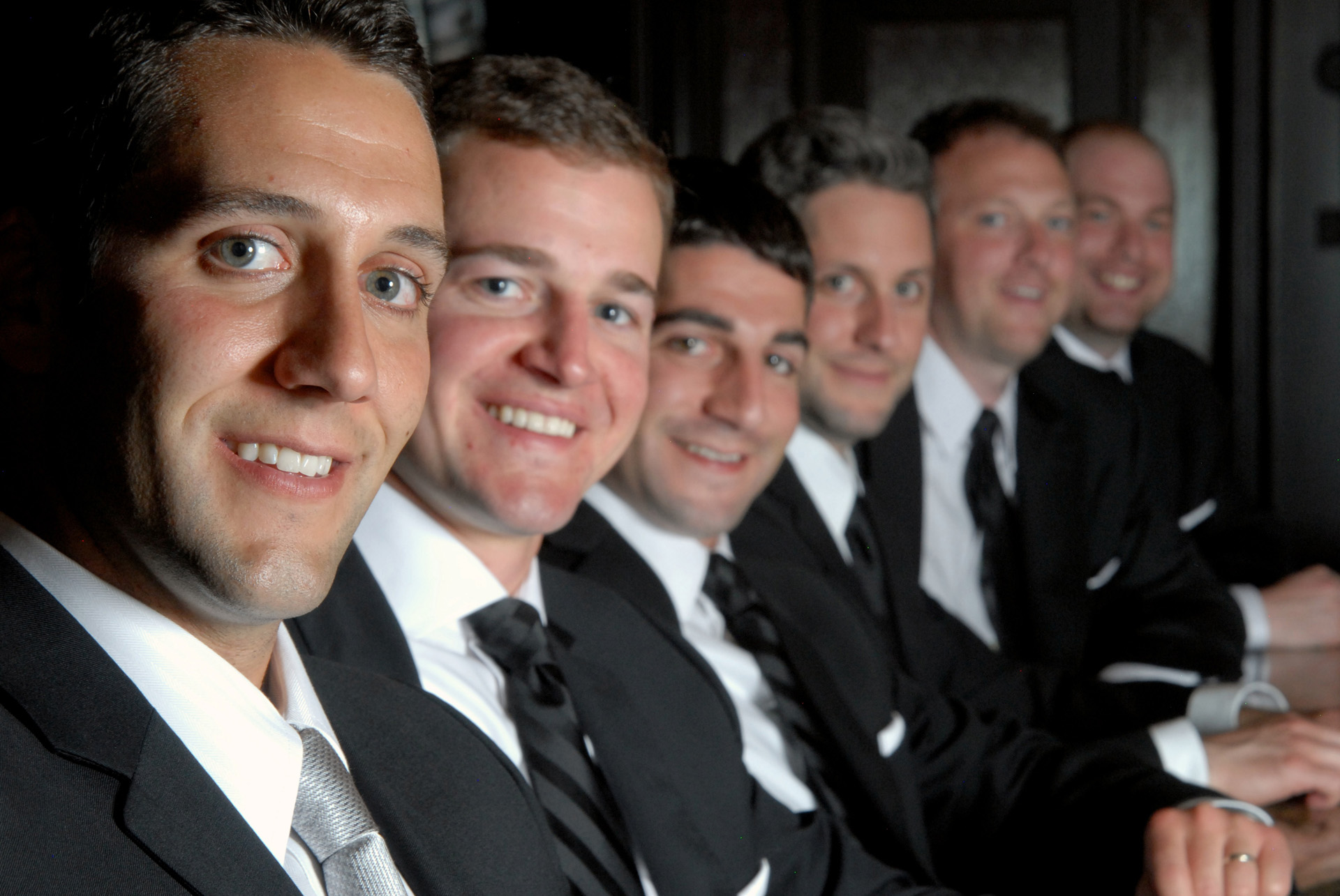 The The Dearborn Inn in Dearborn, Michigan wedding photographer's photo of the groom and his groomsmen waiting at the bar at Dearborn's historic Dearborn Inn for wedding photos in Dearborn, Michigan.