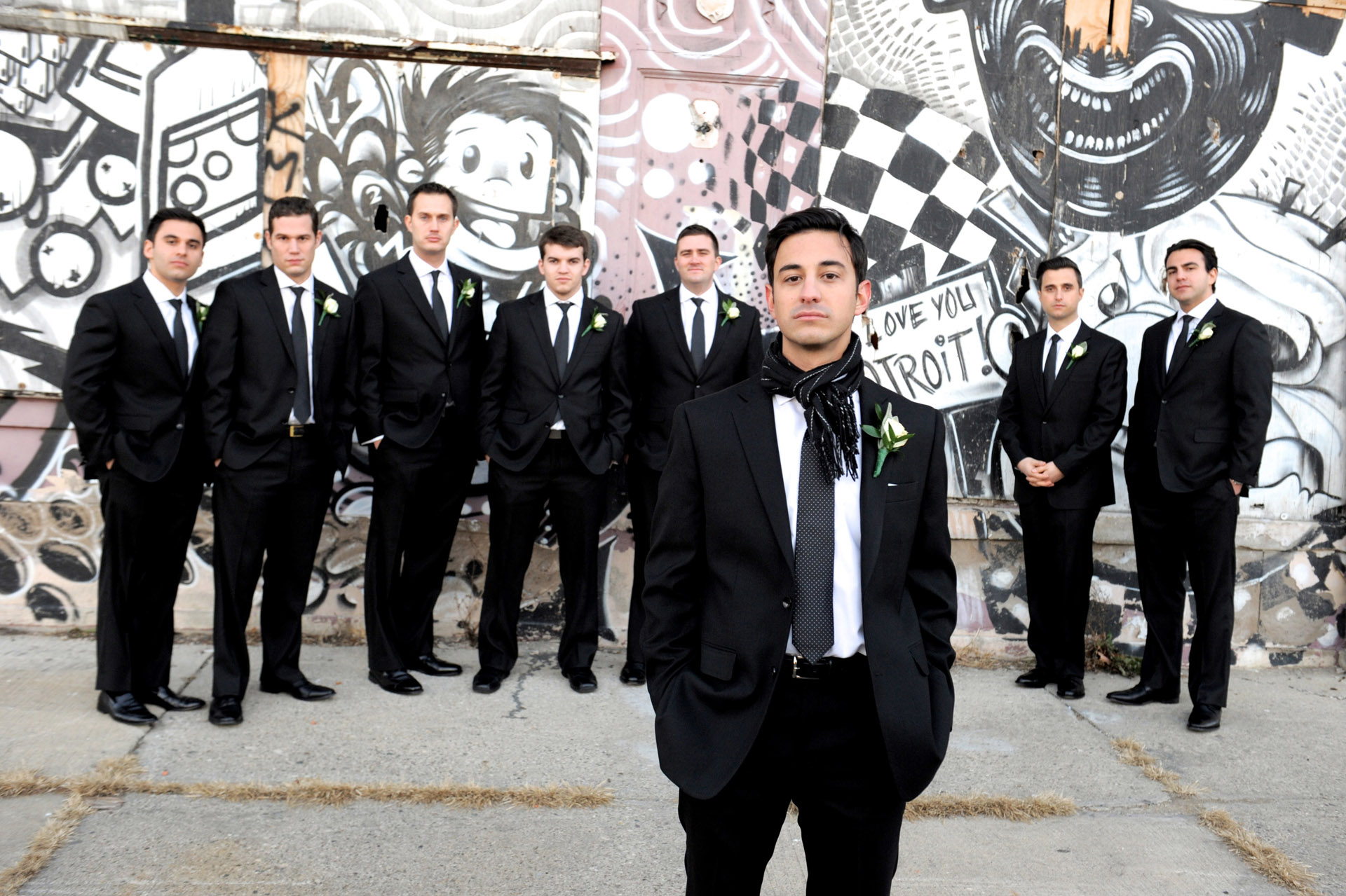 The Historic church Sweetest Heart of Mary and the Dearborn Inn of Detroit's historic church in Detroit and Dearborn, Michigan wedding photographer's  photo of the groom and his groomsmen near the Detroit's historic train station for wedding photos in Detroit, Michigan with local graffiti art.