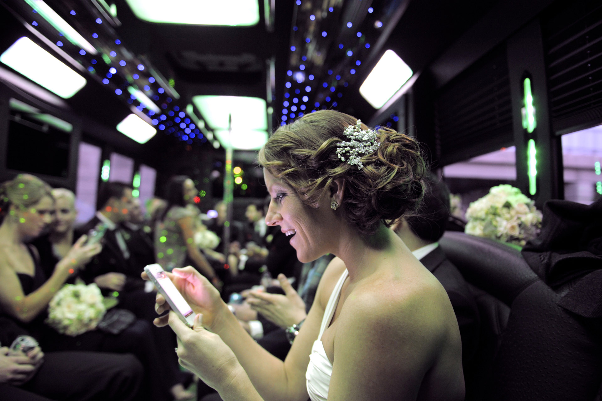 The Historic church Sweetest Heart of Mary and the Dearborn Inn of Detroit's historic church in Detroit and Dearborn, Michigan wedding photographer's of the bride changing her Facebook status in the limo bus on her way to her wedding reception at the Dearborn Inn in Dearborn, Michigan.