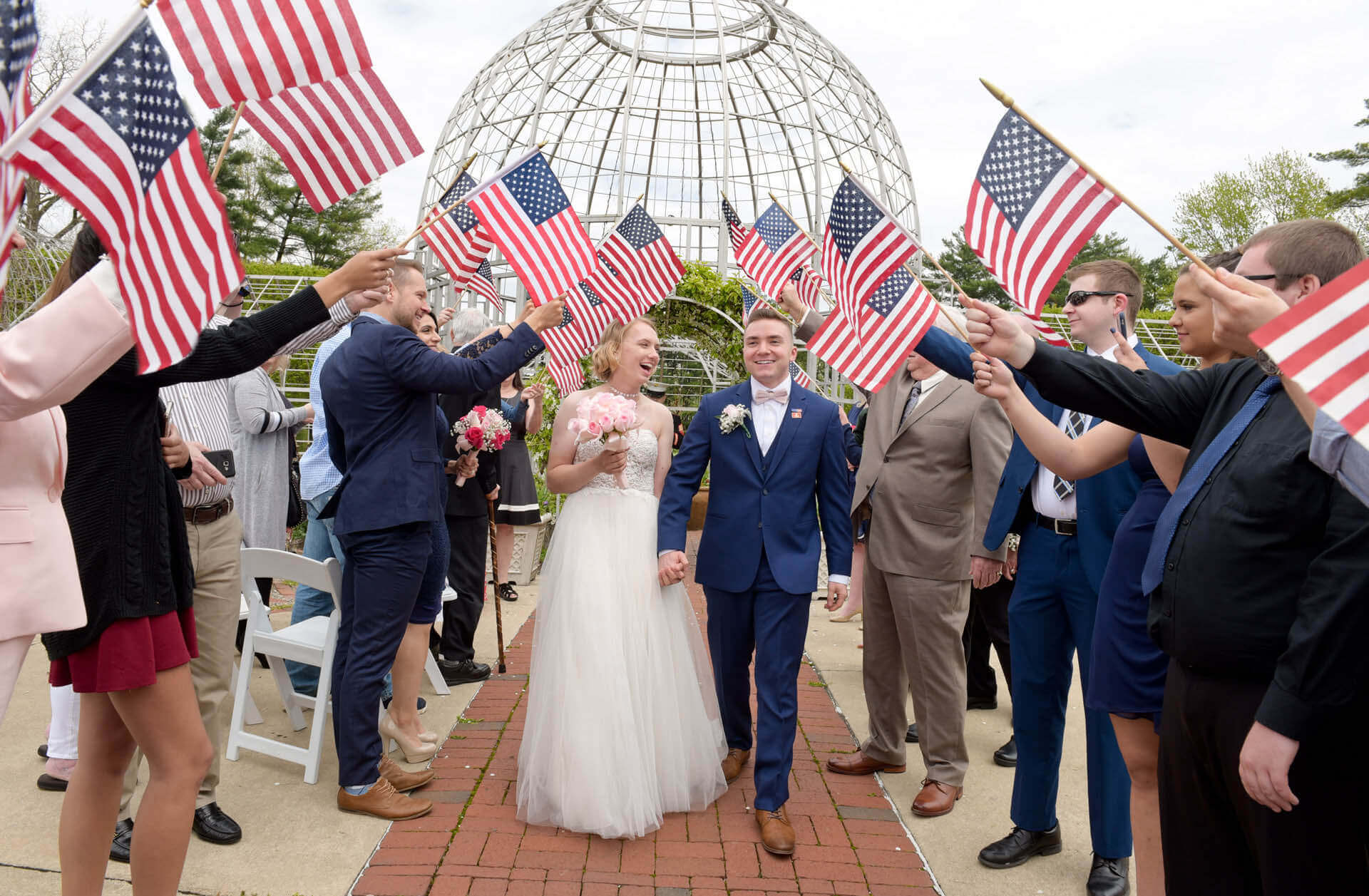 Fresh from Marine bootcamp, this bride walks down a makeshift aisle of American Flags at Taylor's Botanical Garden and Conservatory.