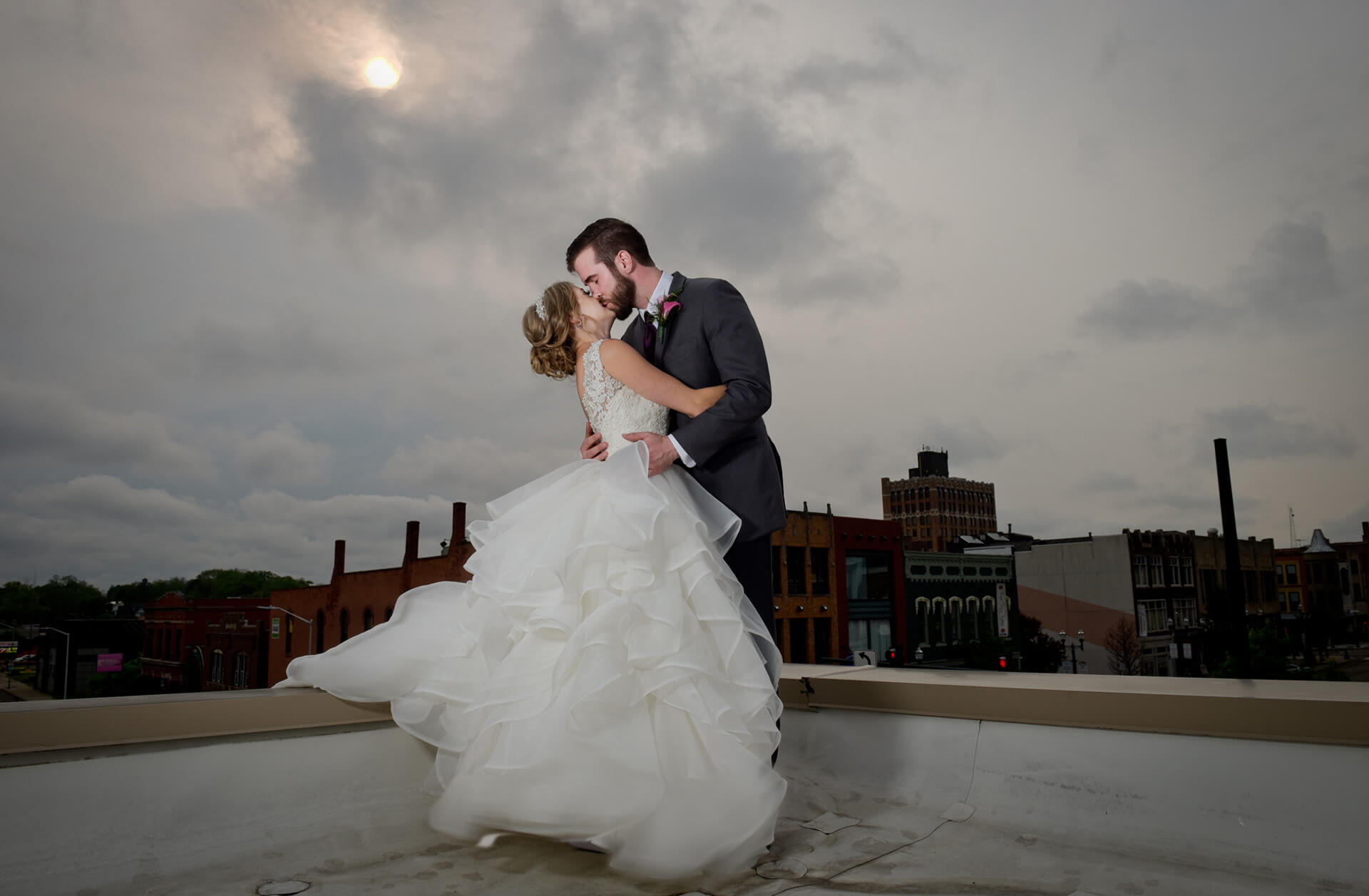 A couple kissing on top of the Crofoot Ballroom during a storm in Pontiac, Michigan just after their wedding is in part what has gotten me voted best Michigan wedding photographer 10 years in a row.