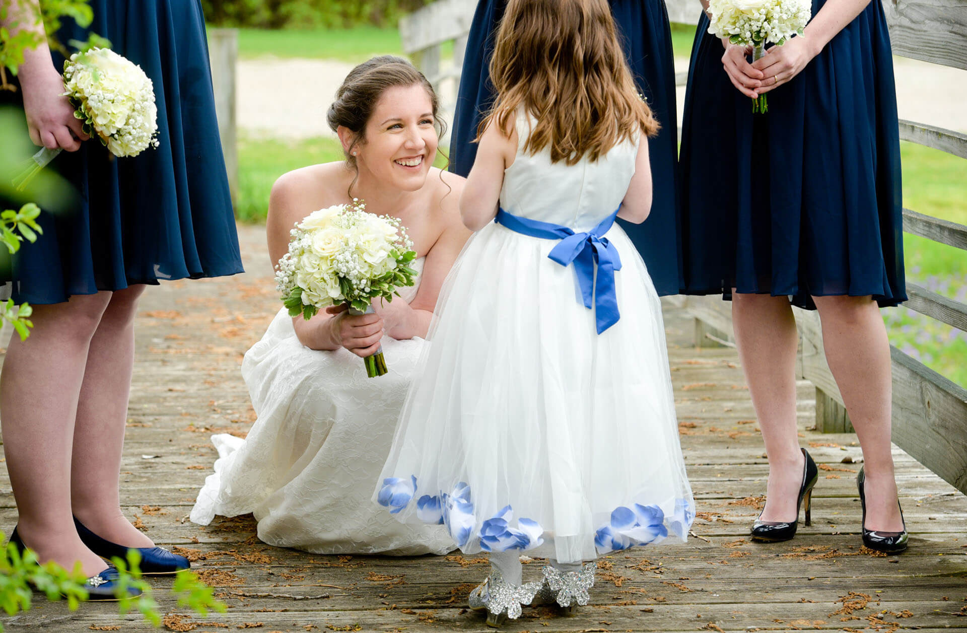 A bride tries to cajole a reticent flower girl at her Stonebridge Golf Club wedding in Ann Arbor, Michigan.