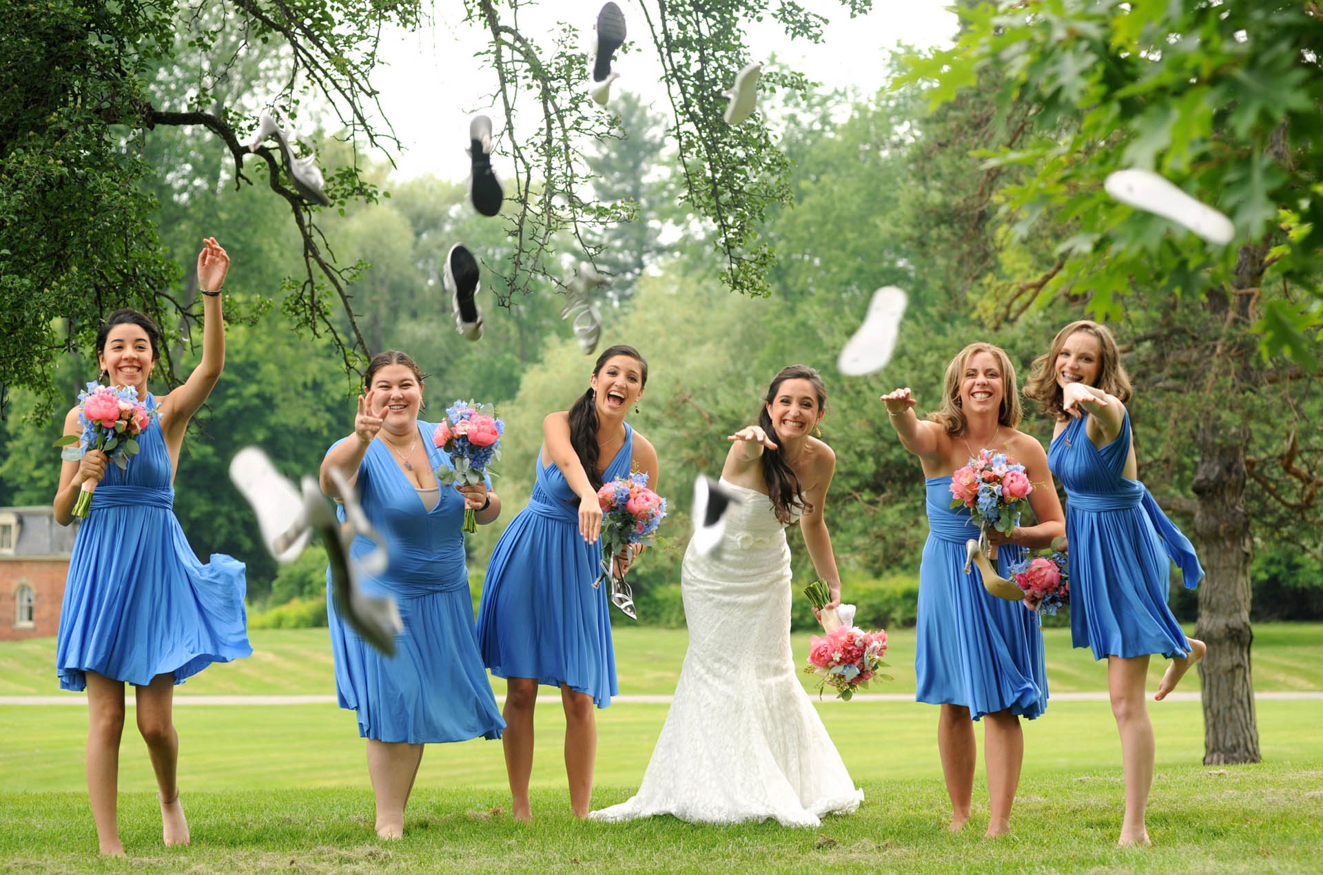 michigan wedding photographer takes funny photos of wedding parties throwing their shoes at the photographer at Addison Oaks.