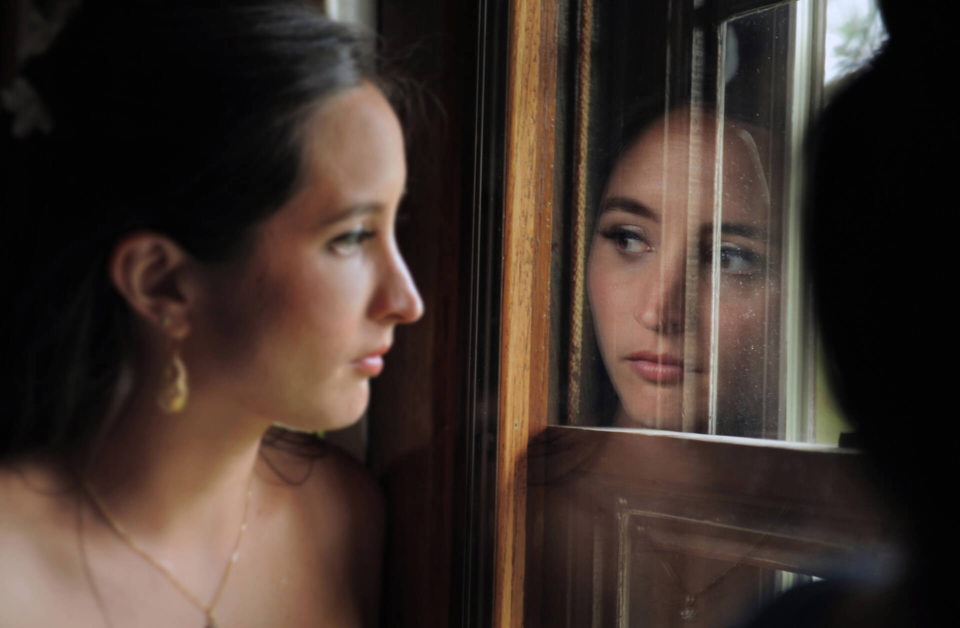 Michigan wedding photographer takes candid photos of a bride nervously looking out a window watching guests arrive for her Addison Oaks wedding in Romeo, Michigan.