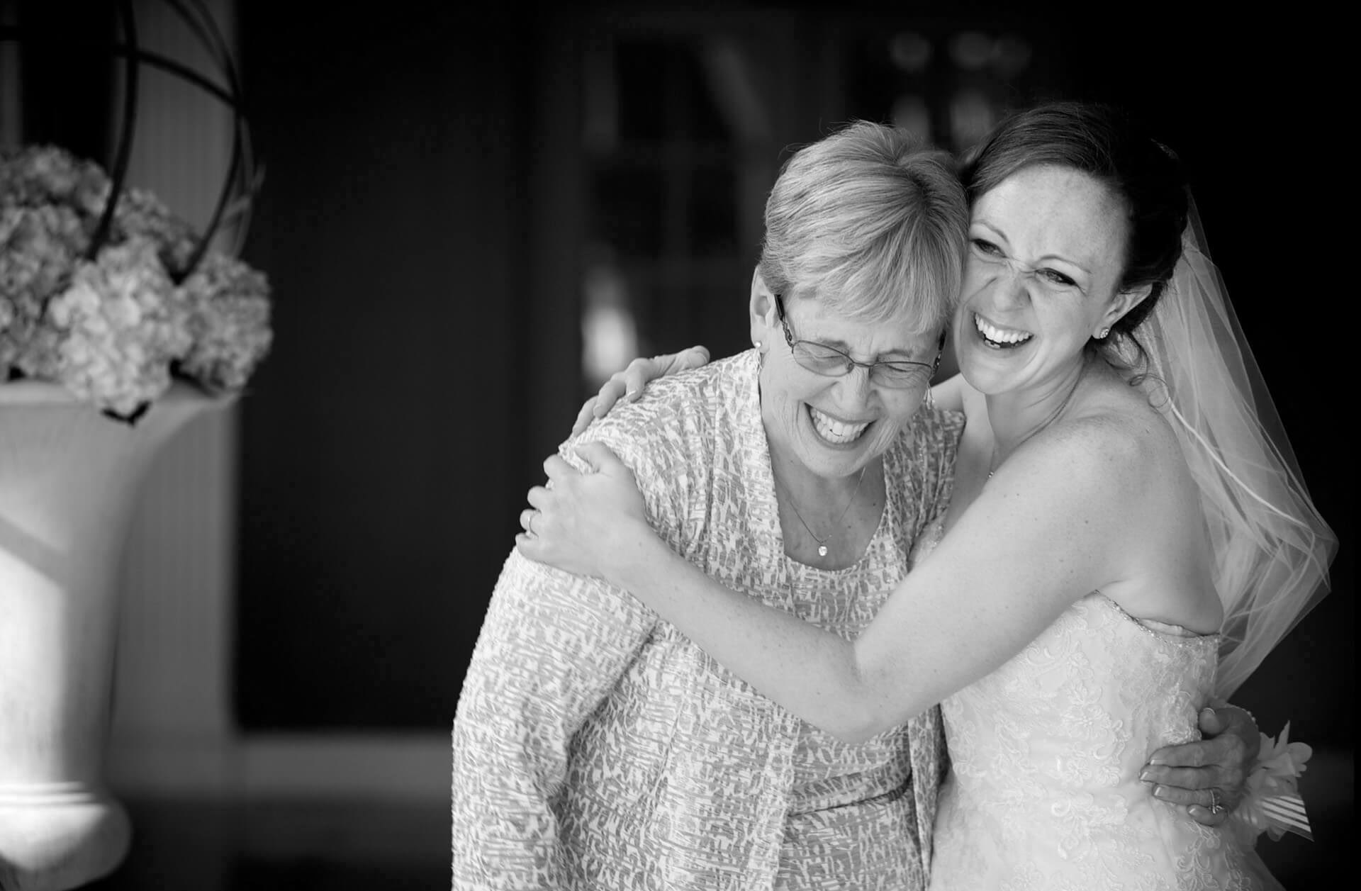 Michigan wedding photographer takes photojournalists photos of a bride hugging her grandmother after her wedding.