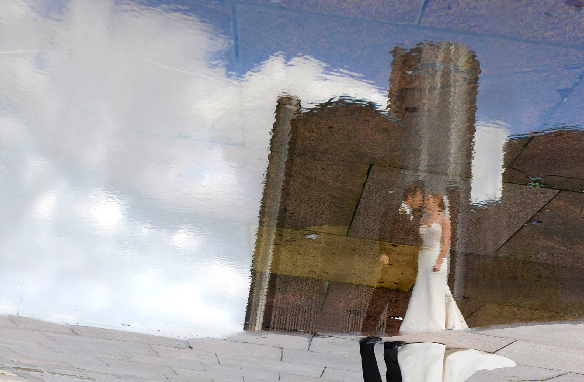michigan wedding photographer shoots a Detroit wedding couple in a reflection of Detroit's landmark; the Renaissance Center.