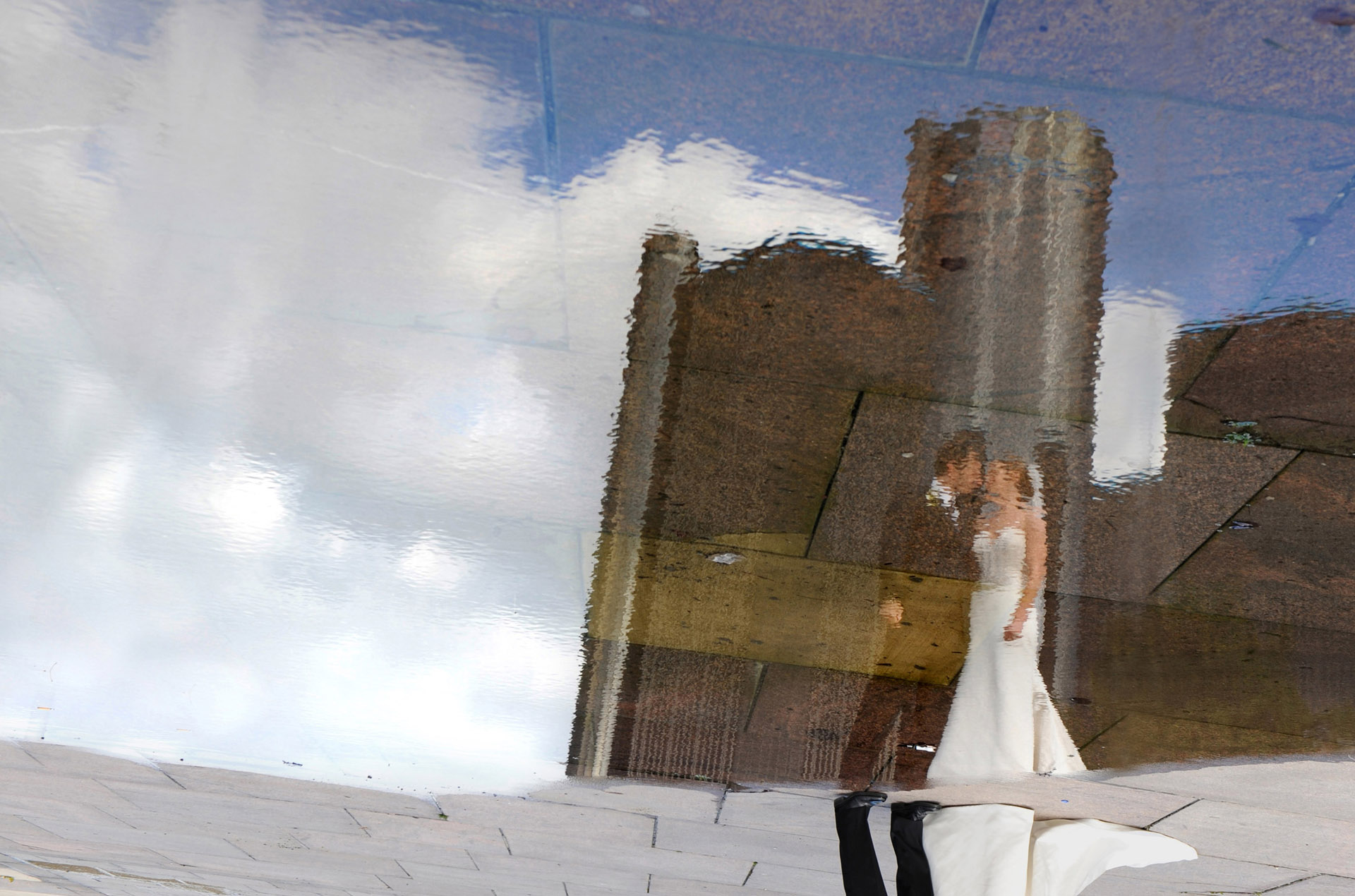 michigan wedding photographer shoots a Detroit wedding couple in a reflection of Detroit's landmark; the Renaissance Center.